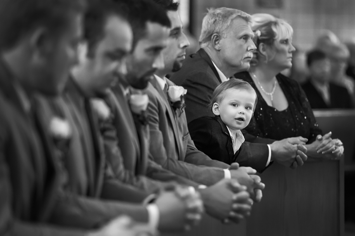 Little boy takes a sneek peek during church ceremony, photo by Amber Henry Photography, Michigan