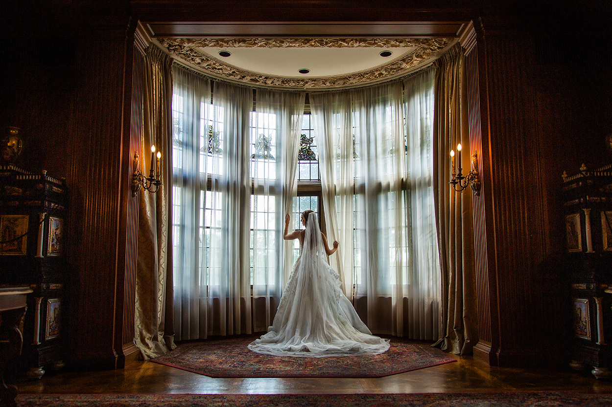 Portrait showing back of bridal gown against elegant window by Amber Henry Photography, Michigan