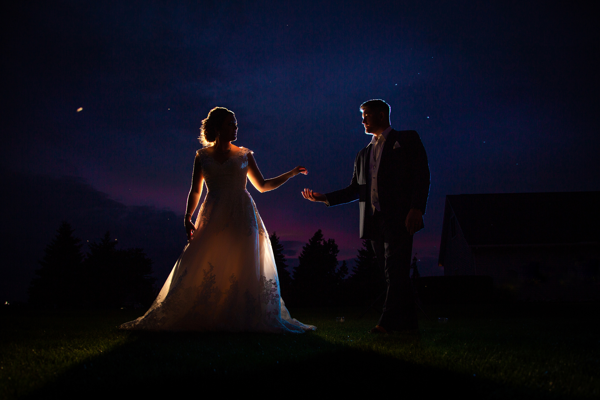 Backlit bride with groom under night sky - photo by Amber Henry Photography