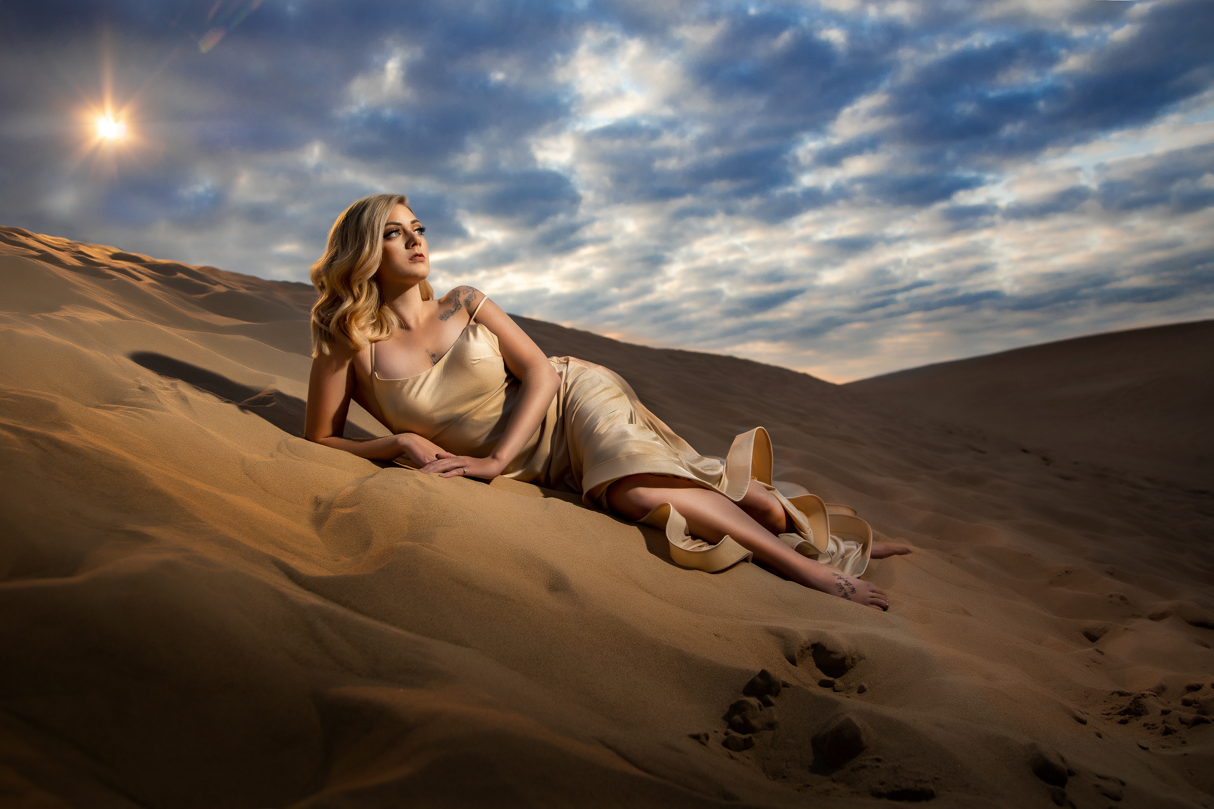 Bride in gold silk slip lying on sand dune - photo by Amber Henry - Michigan wedding photographer