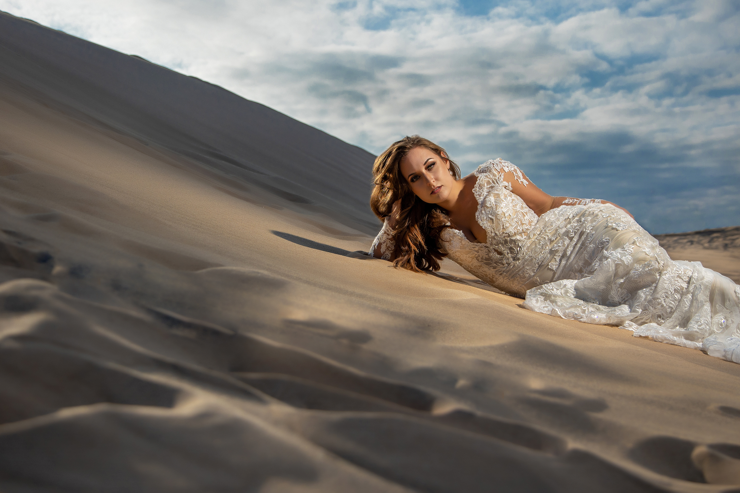 Portrait of bride in lace wedding dress lying on sand dune - photo by Amber Henry - Michigan