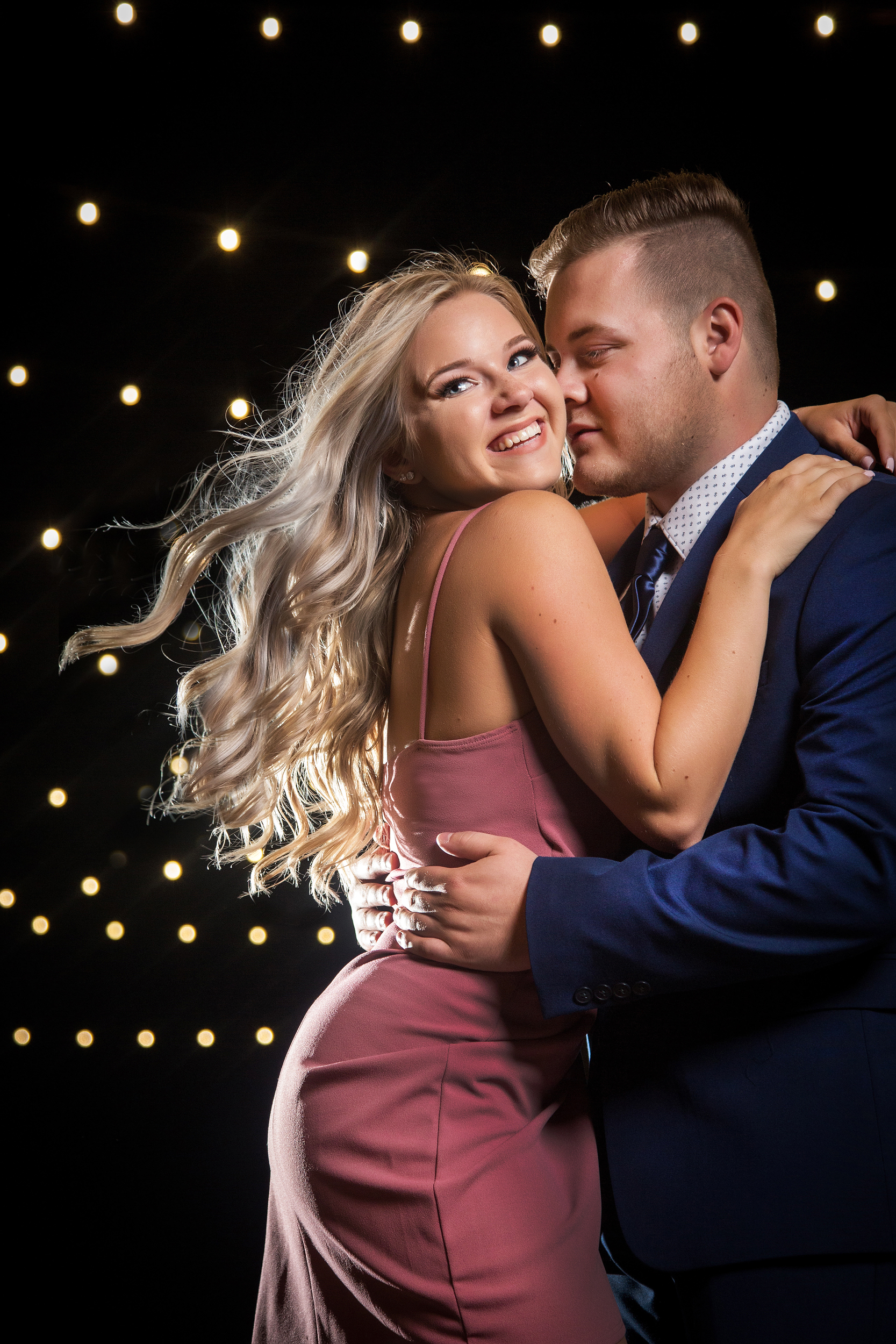 Engagement photo of man and smiling woman with long blonde hair - photo by Amber Henry Photography