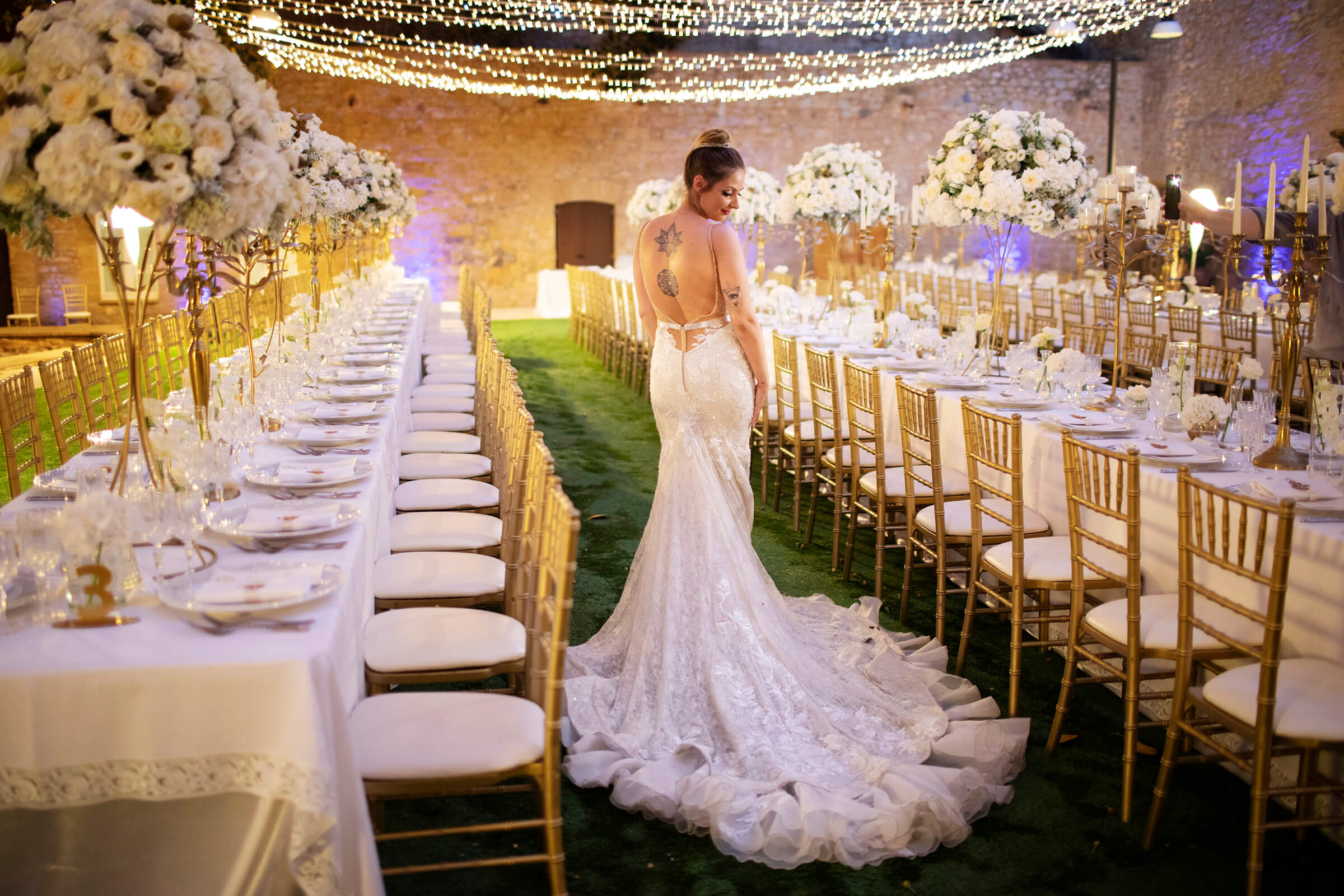 Bride against set reception tables - photo by Nino Lombardo Photographer