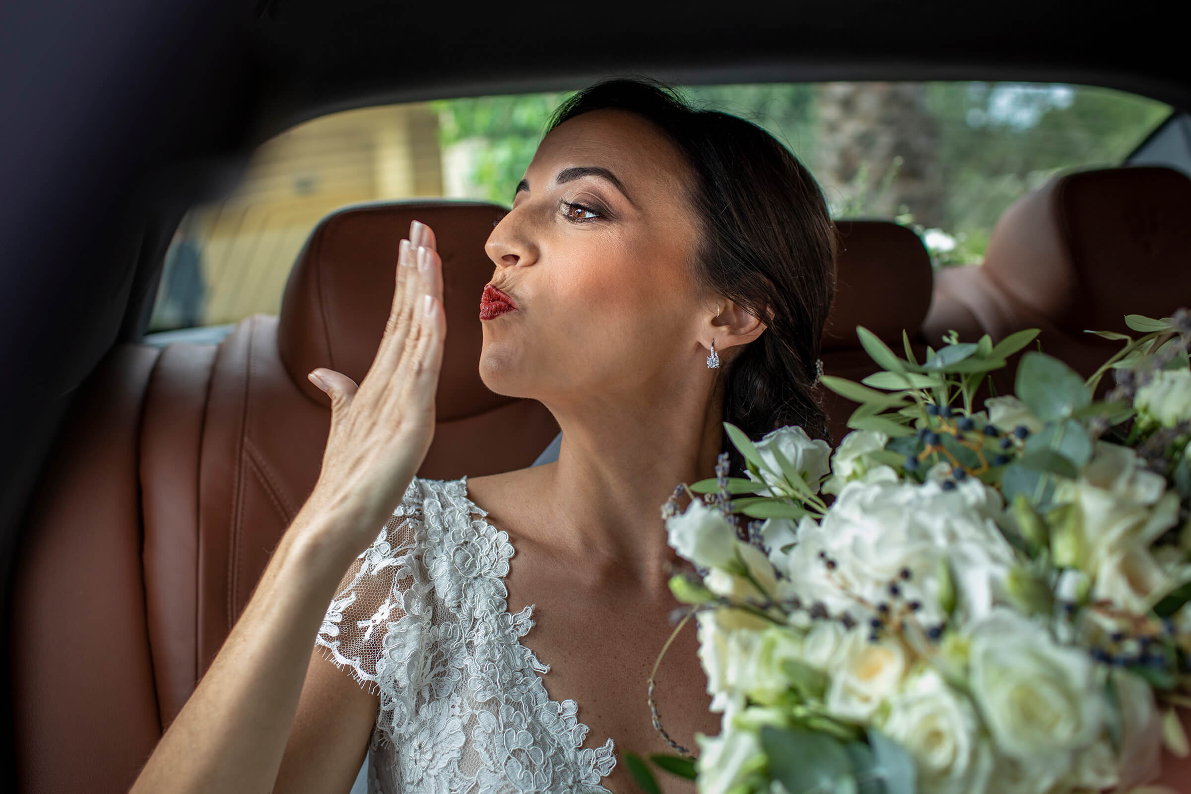 Bride with bouquet blowing kiss from limo - photo by Nino Lombardo Photographer