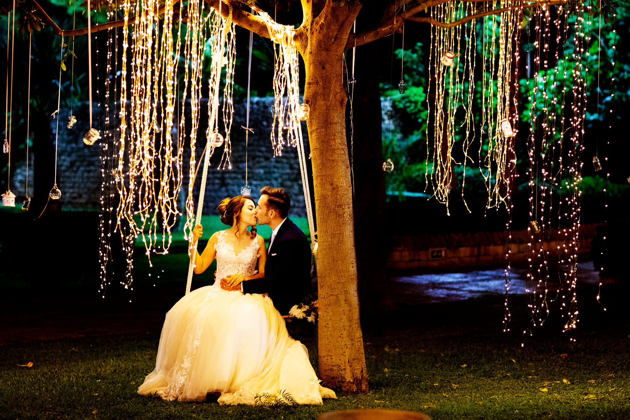 Couple kiss under hanging light strands - photo by Nino Lombardo Photographer