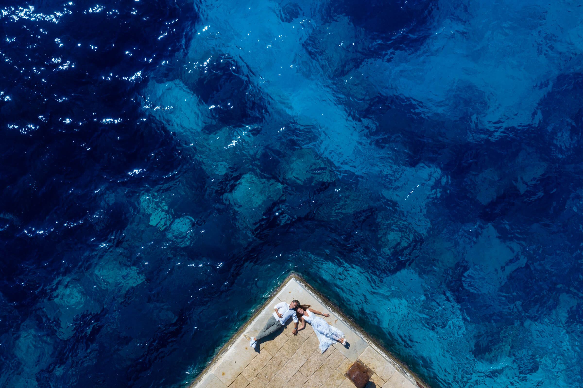 Couple lying at corner of pier over aquamarine waters in Sicily - photo by Nino Lombardo Photographer