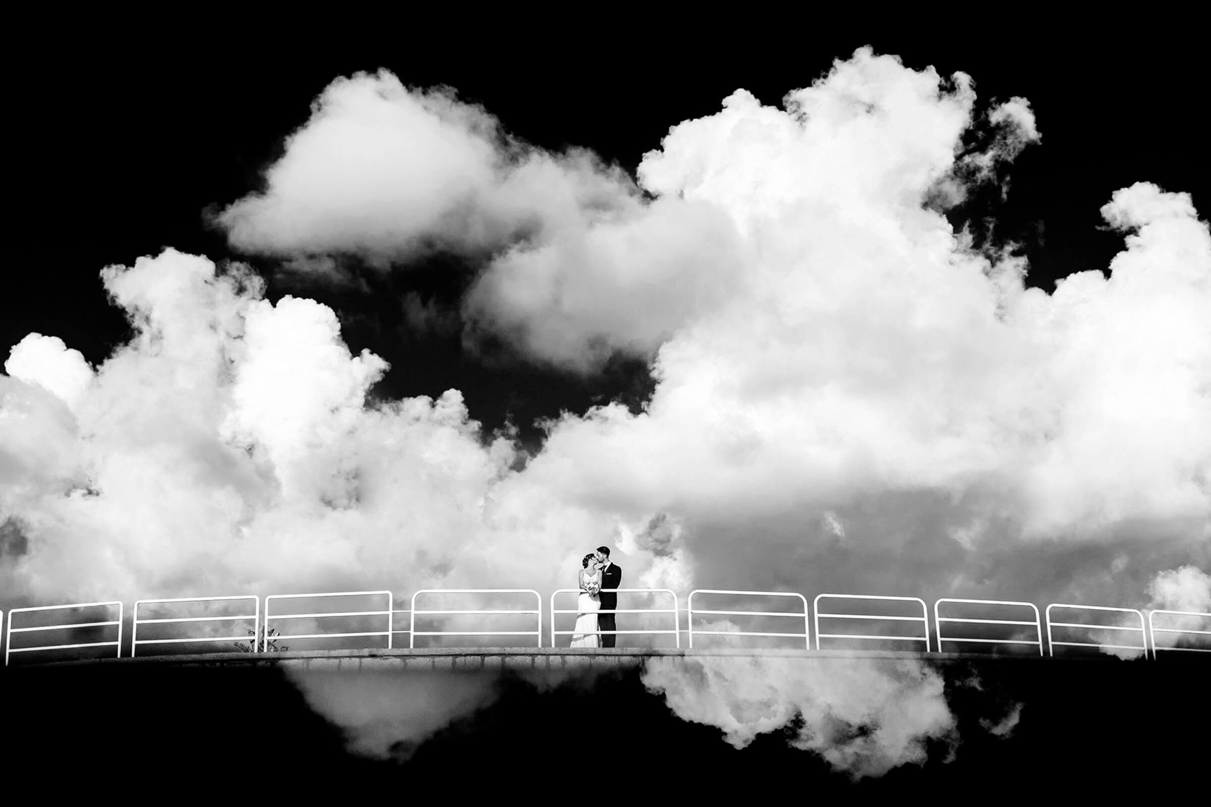 Landscape view of couple on bridge against cumulus cloud sky - photo by Nino Lombardo Photographer