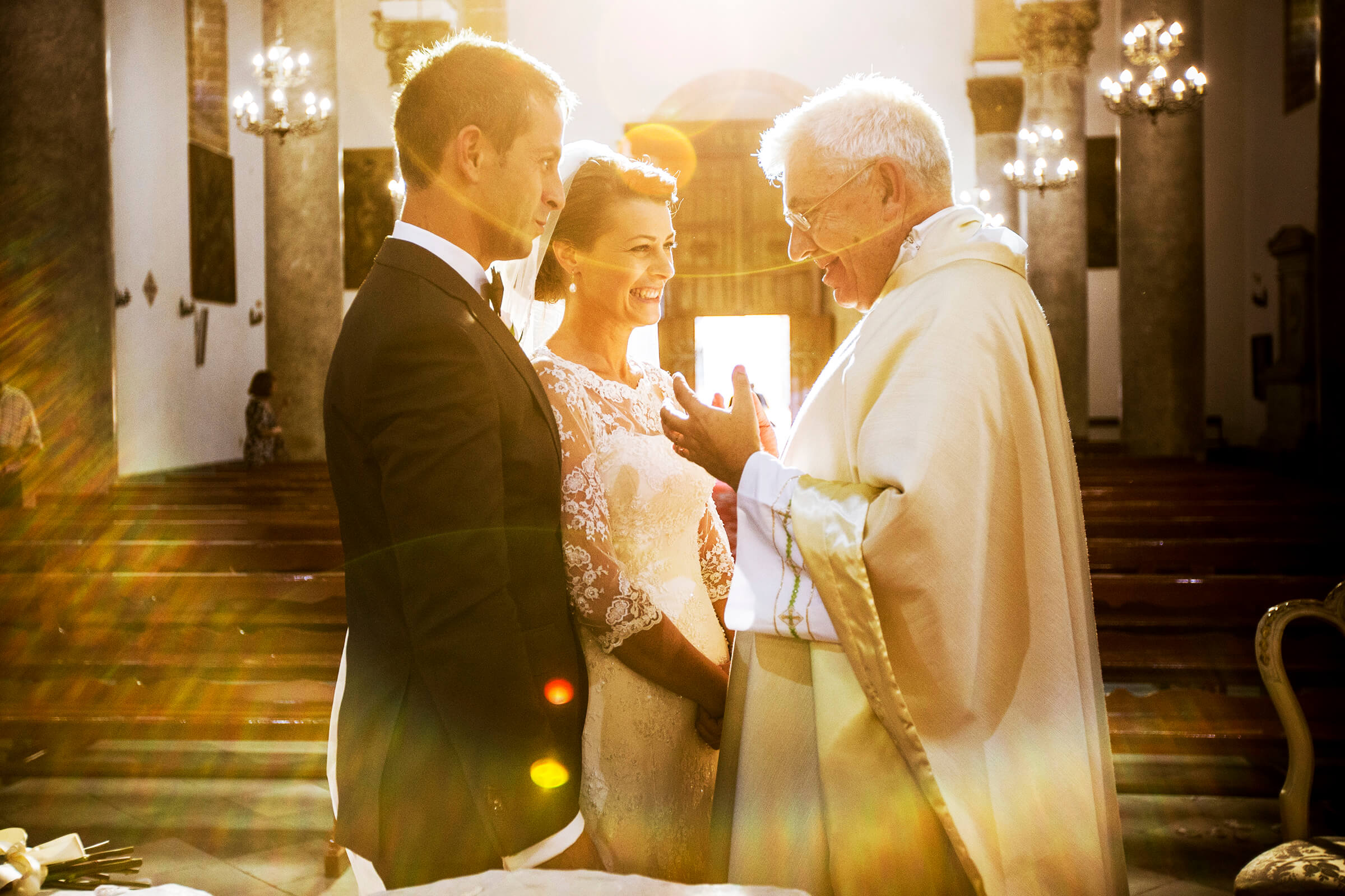 Bride and groom with priest in halo light - photo by Nino Lombardo Photographer