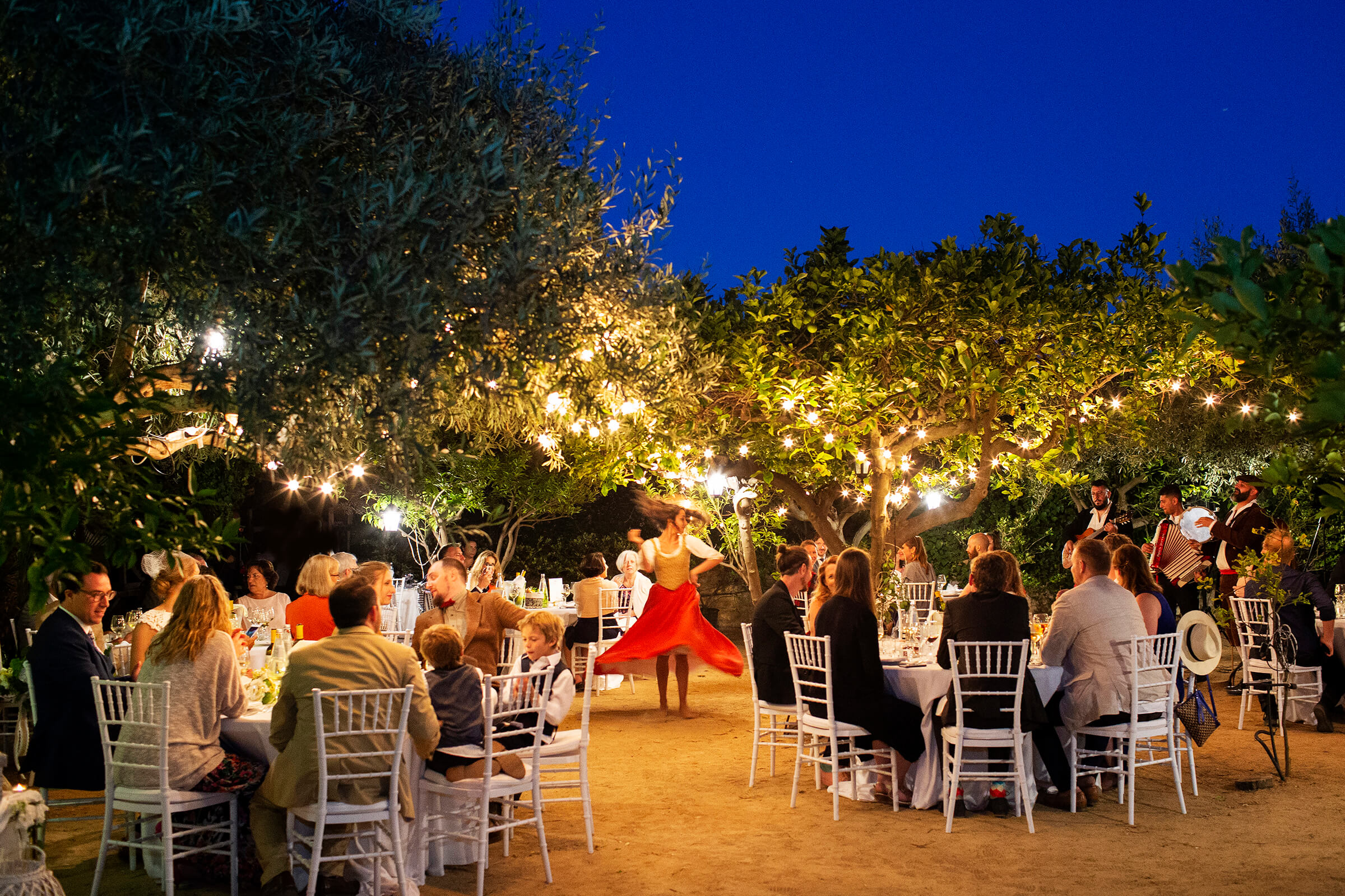 Reception guests enjoy dancer under lighted trees - photo by Nino Lombardo Photographer