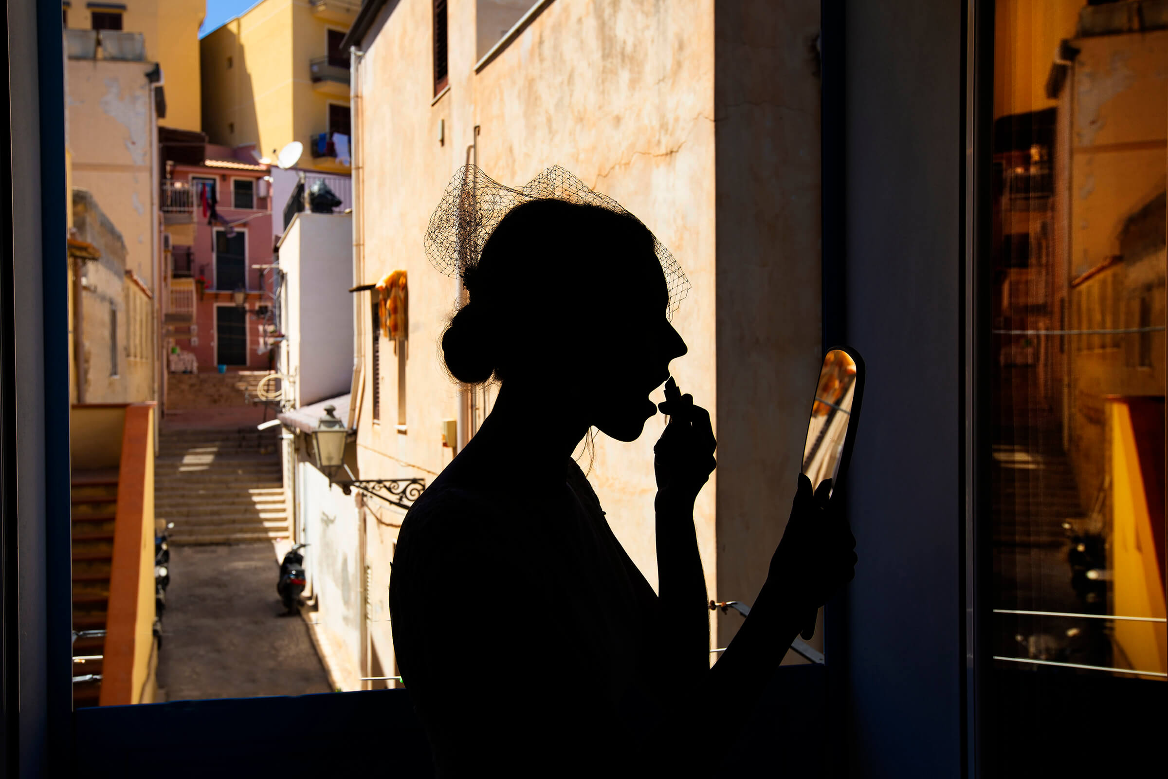 Silhouette bride applying lipstick in Sicilian streetscape - photo by Nino Lombardo Photographer