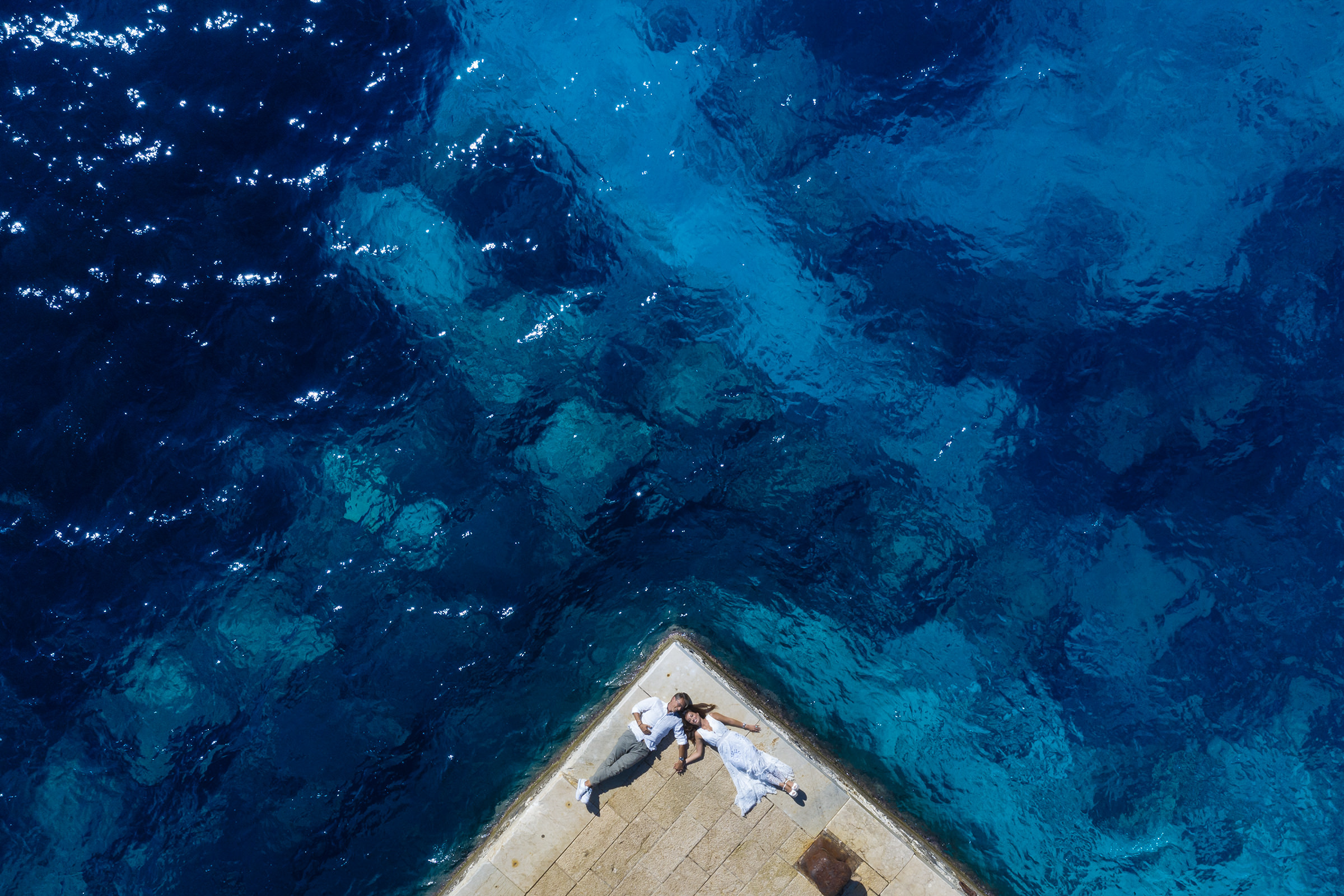 Drone shot of couple over water - photo by Nino Lombardo Photographer