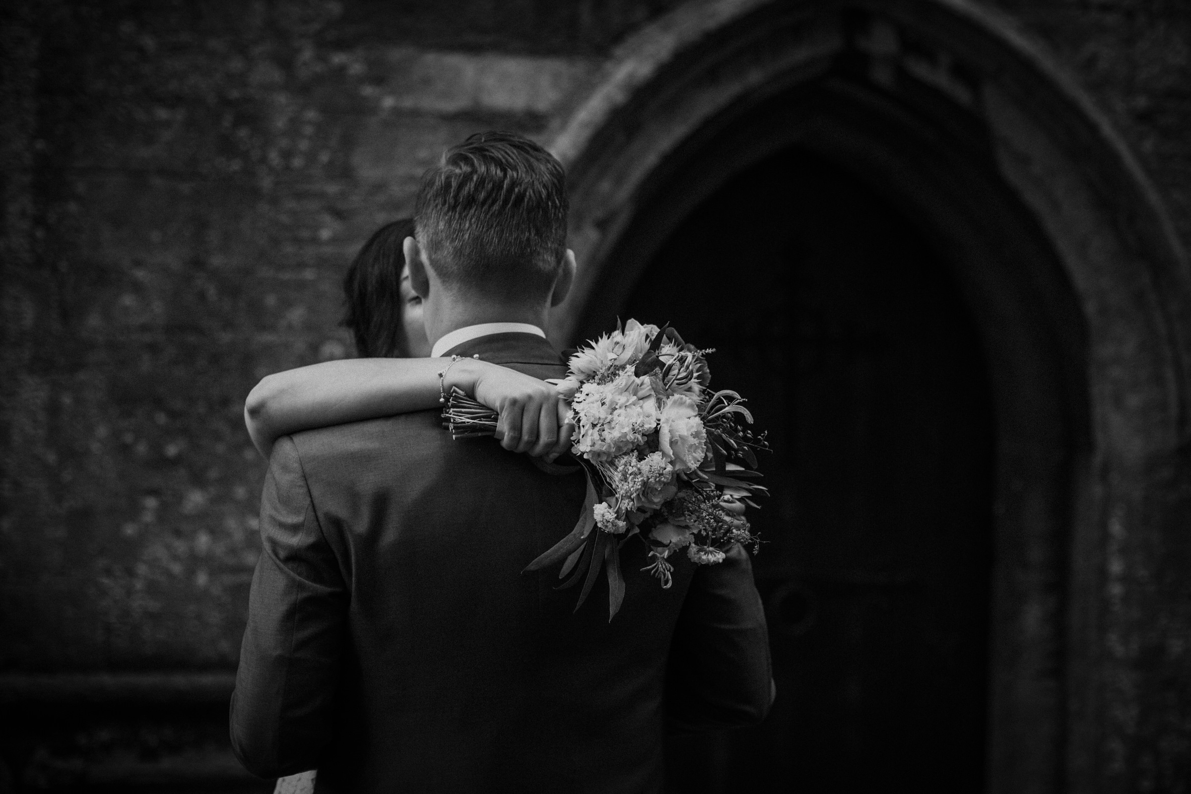 Bouquet shot as bride embraces groom - photo by Tomas Juskaitis Photography