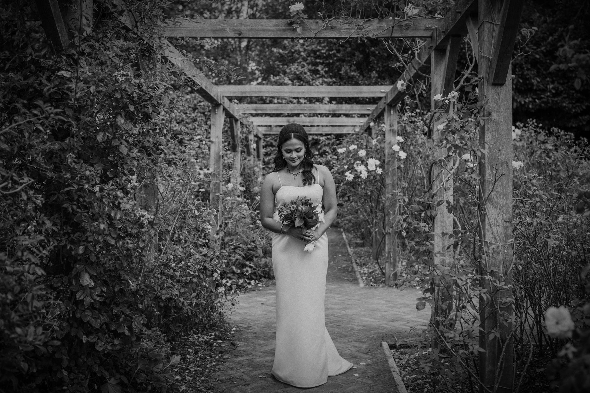 Bride pose with bouquet in floral arbor - photo by Tomas Juskaitis Photography