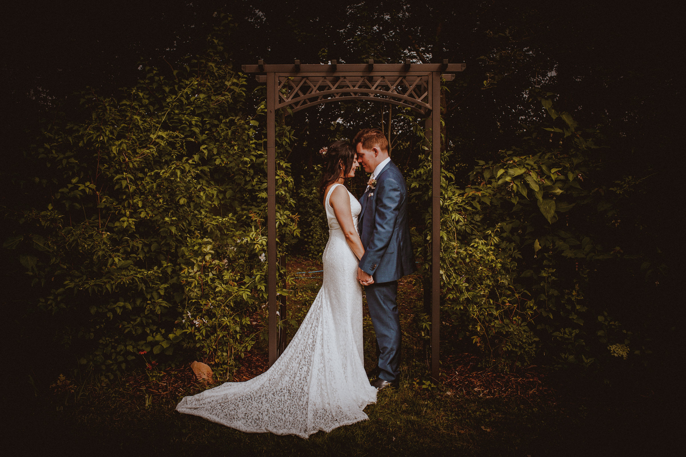 Face to face couple portrait under trellis - photo by Tomas Juskaitis Photography