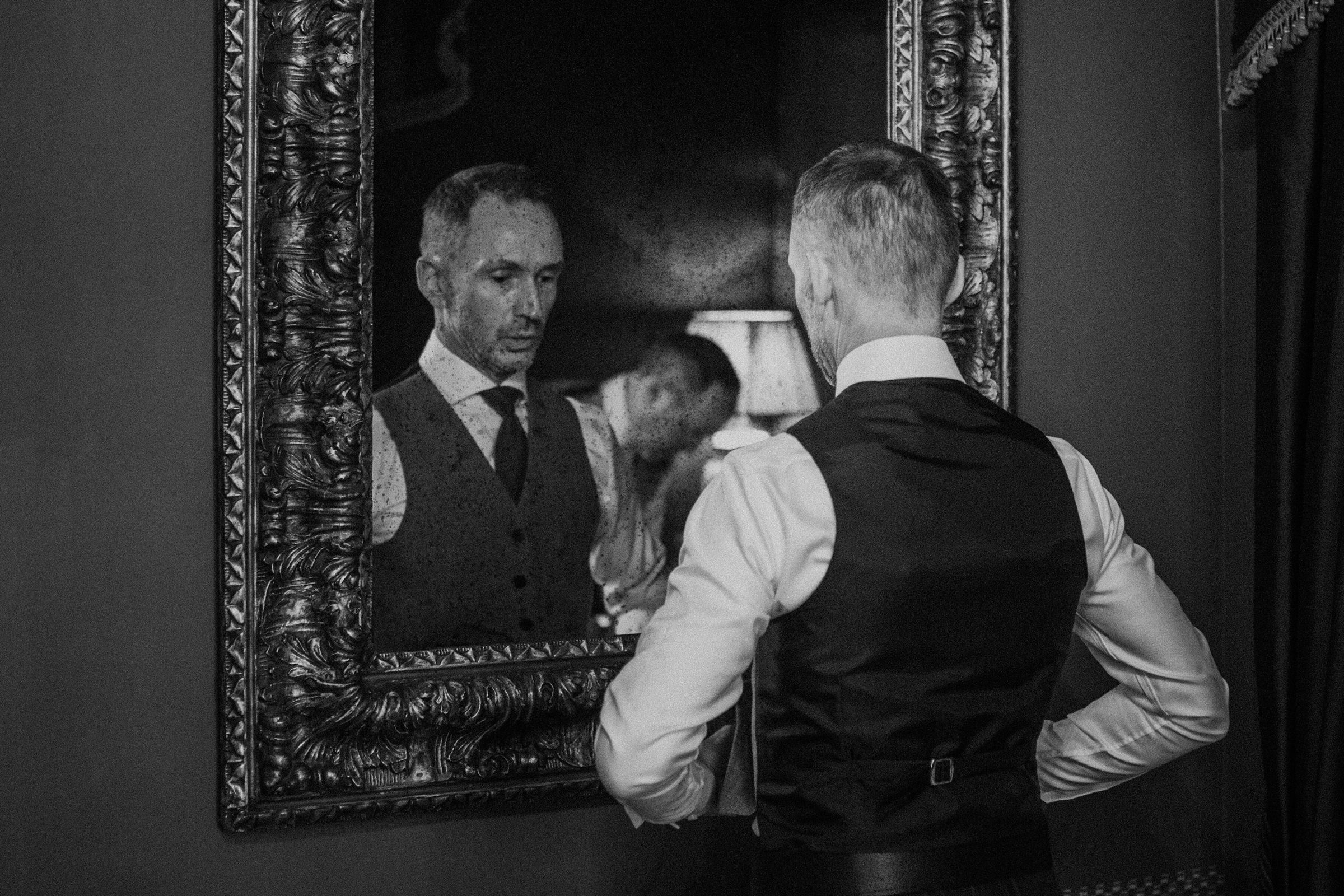Groom primping in ornate mirror - photo by Tomas Juskaitis Photography