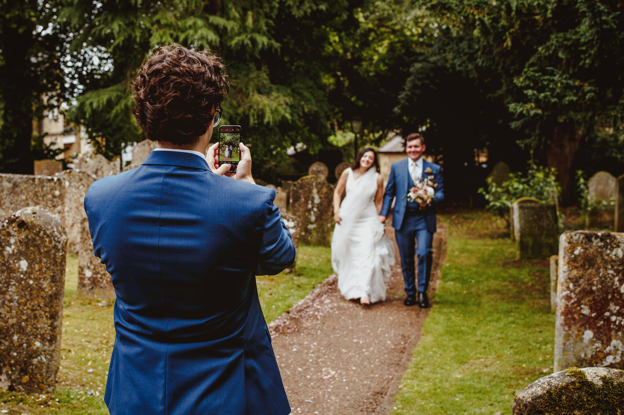 Guest taking photo of approaching bride and groom - photo by Tomas Juskaitis Photography