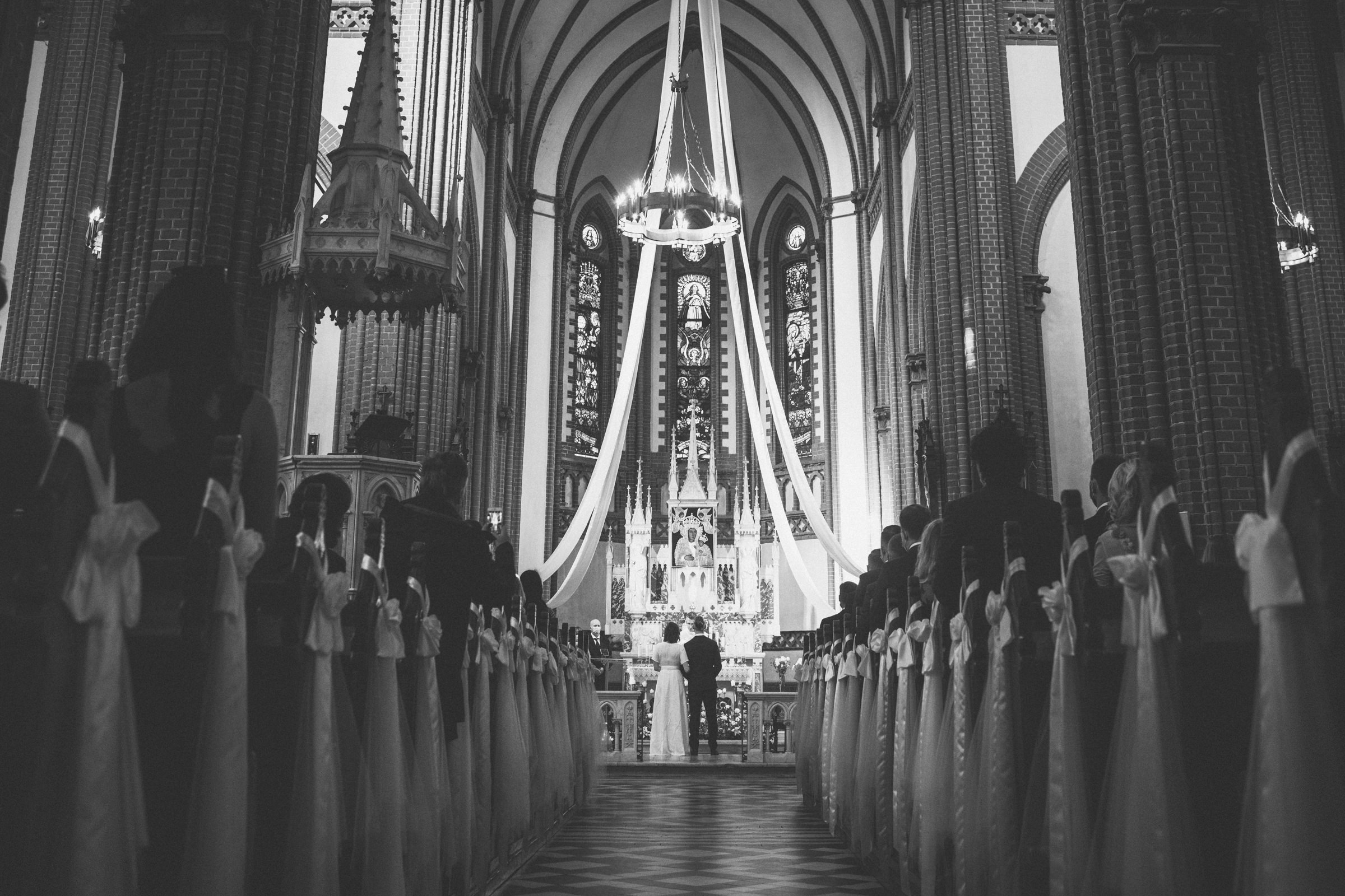 Long view of couple at church altar - photo by Tomas Juskaitis Photography