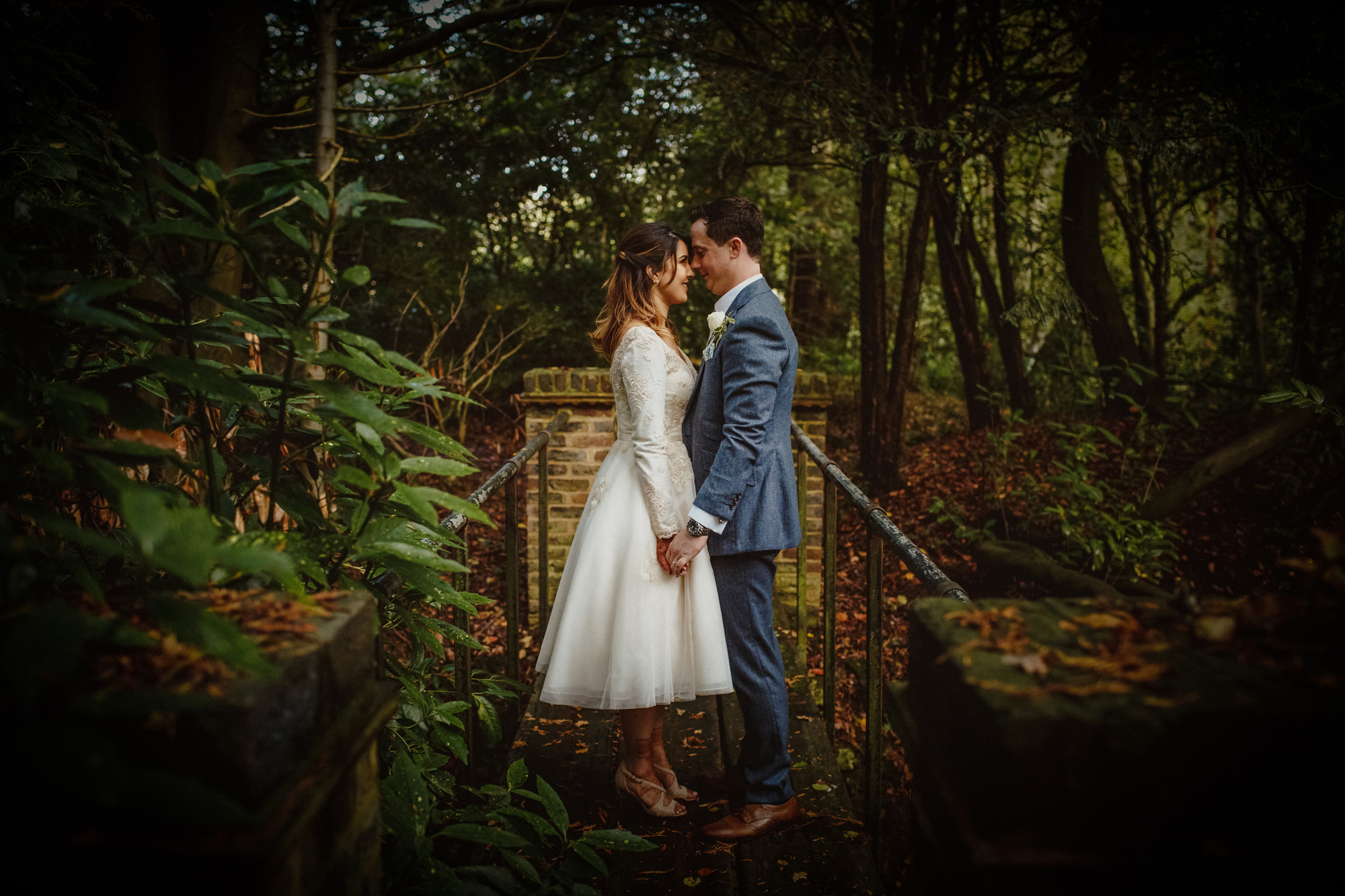 Nose to nose couple portrait in wooded setting - photo by Tomas Juskaitis Photography