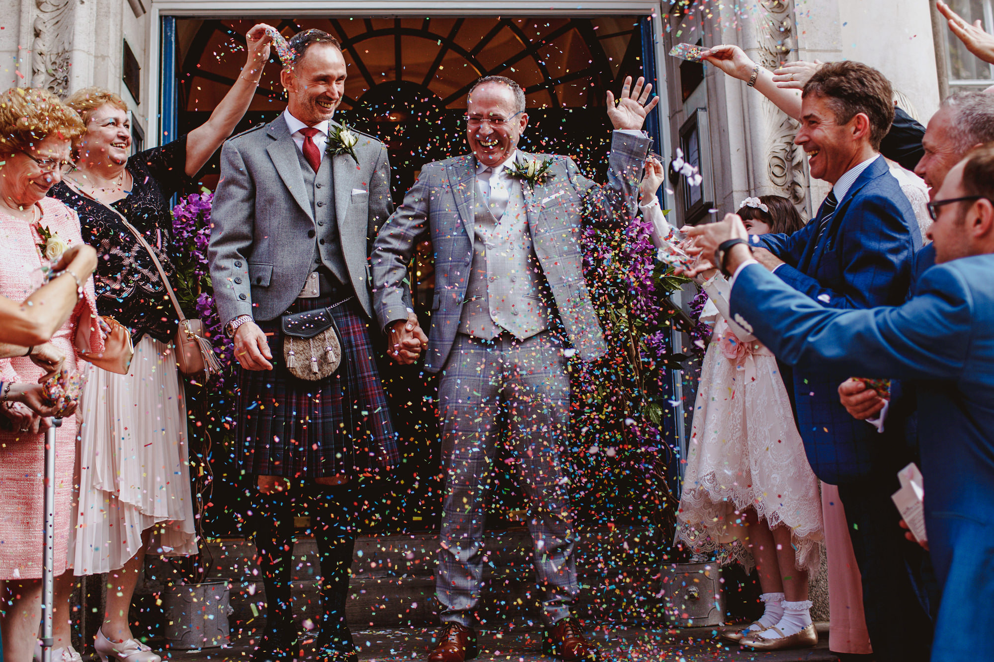 Two grooms exiting to confetti - photo by Tomas Juskaitis Photography