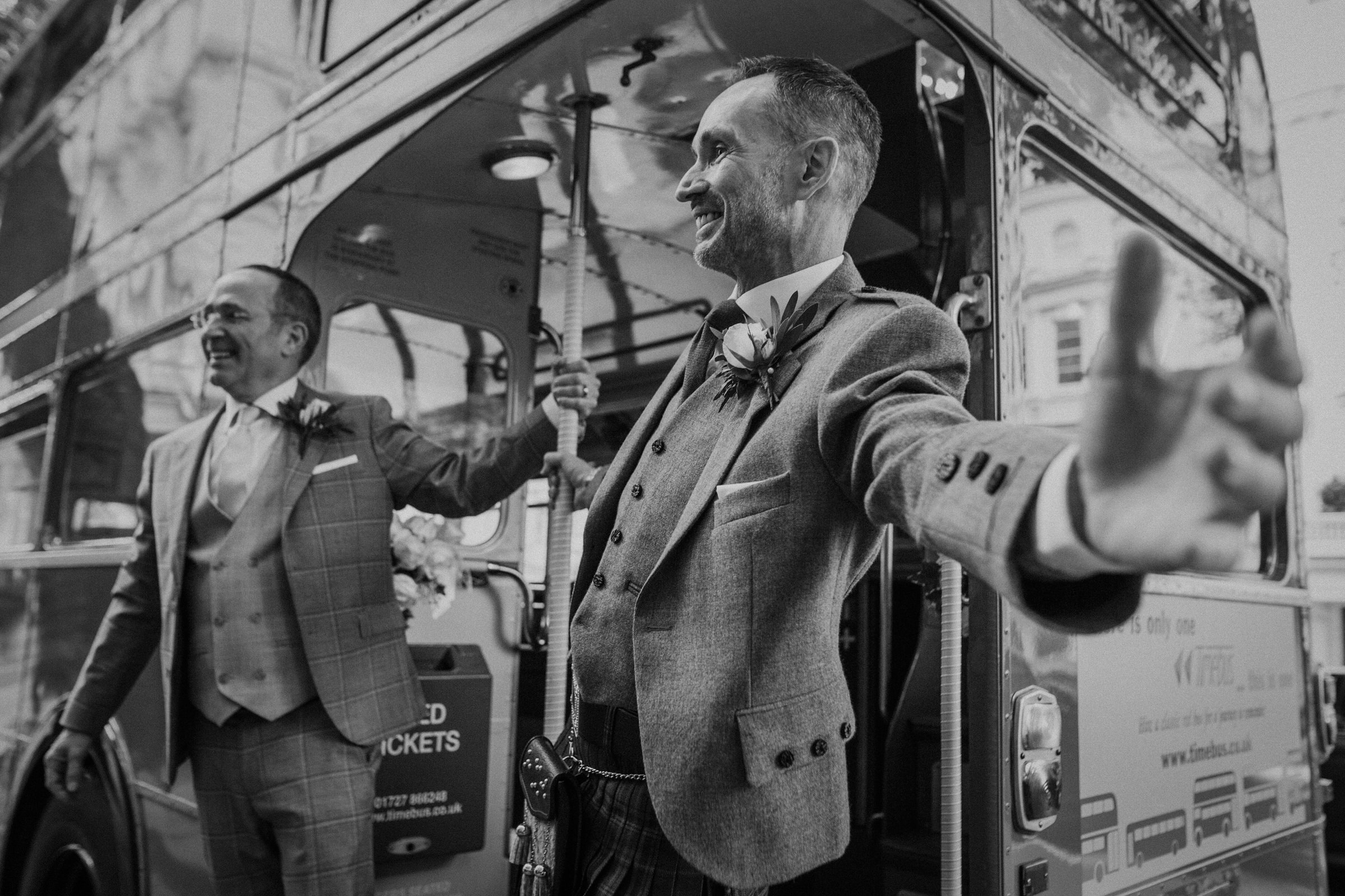 Two grooms posing against bus - photo by Tomas Juskaitis Photography