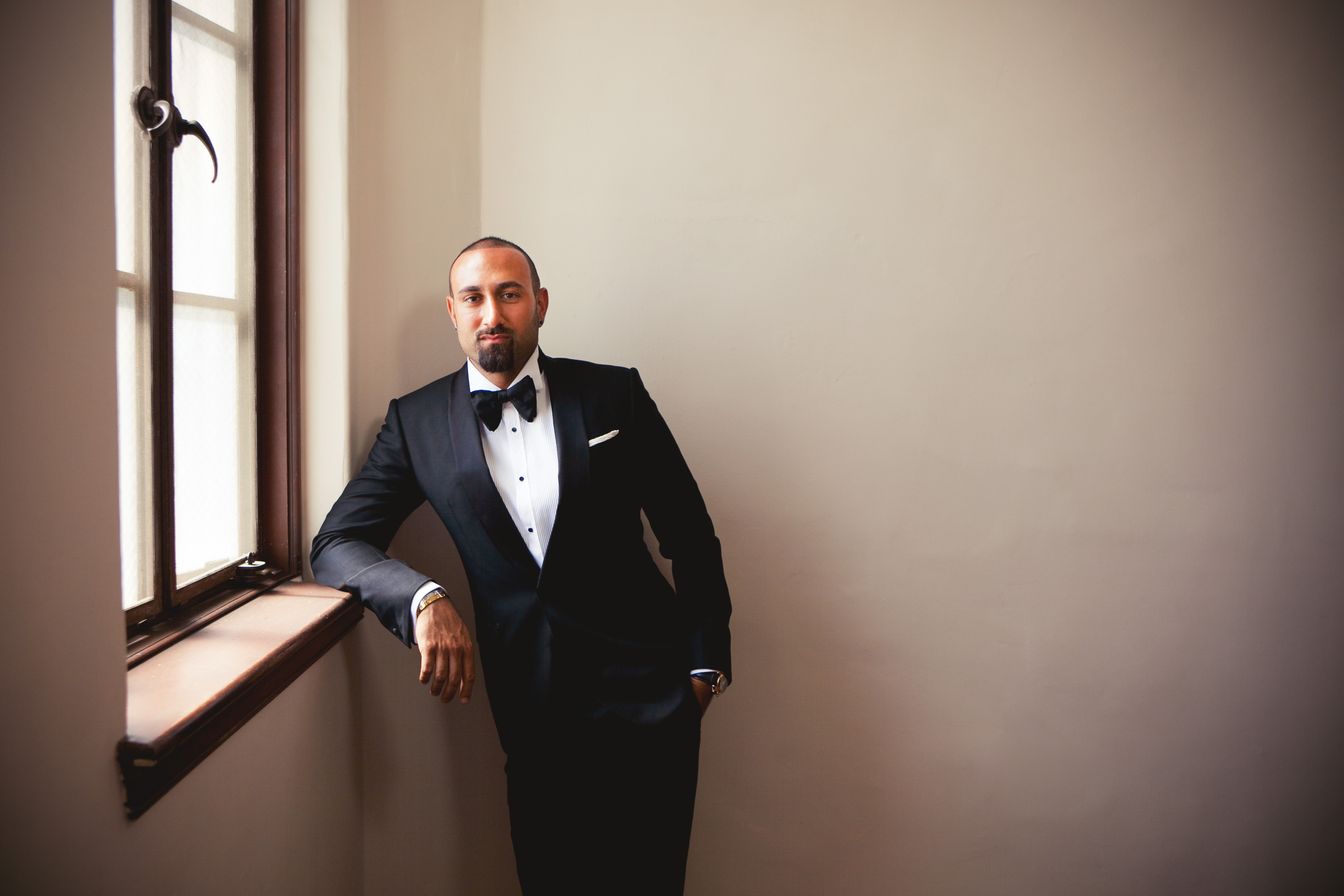 Groom standing at window - photo by Callaway Gable