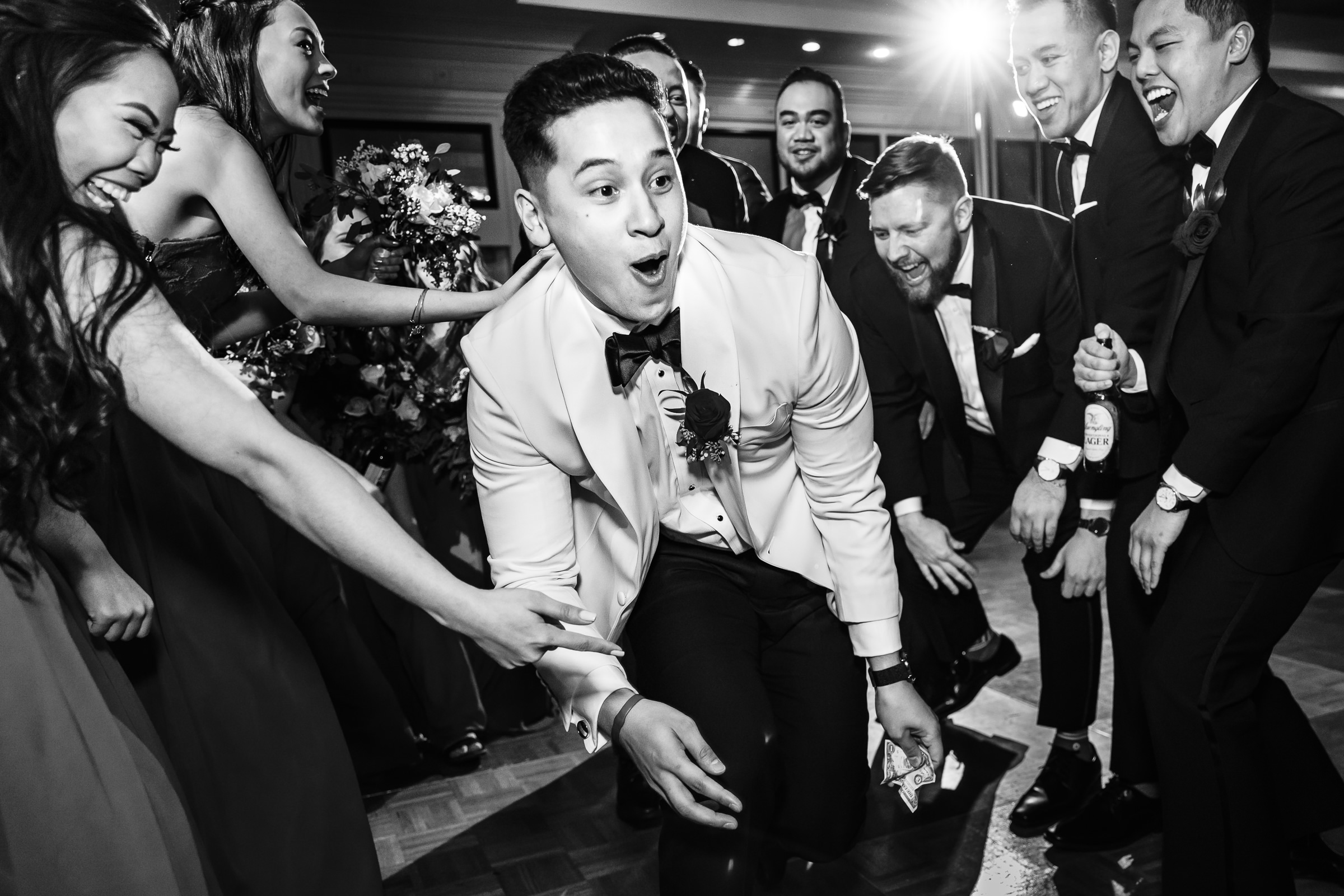 Dancing groom approaches bride with cash in hand - photo by Xiaoqi Li Photography