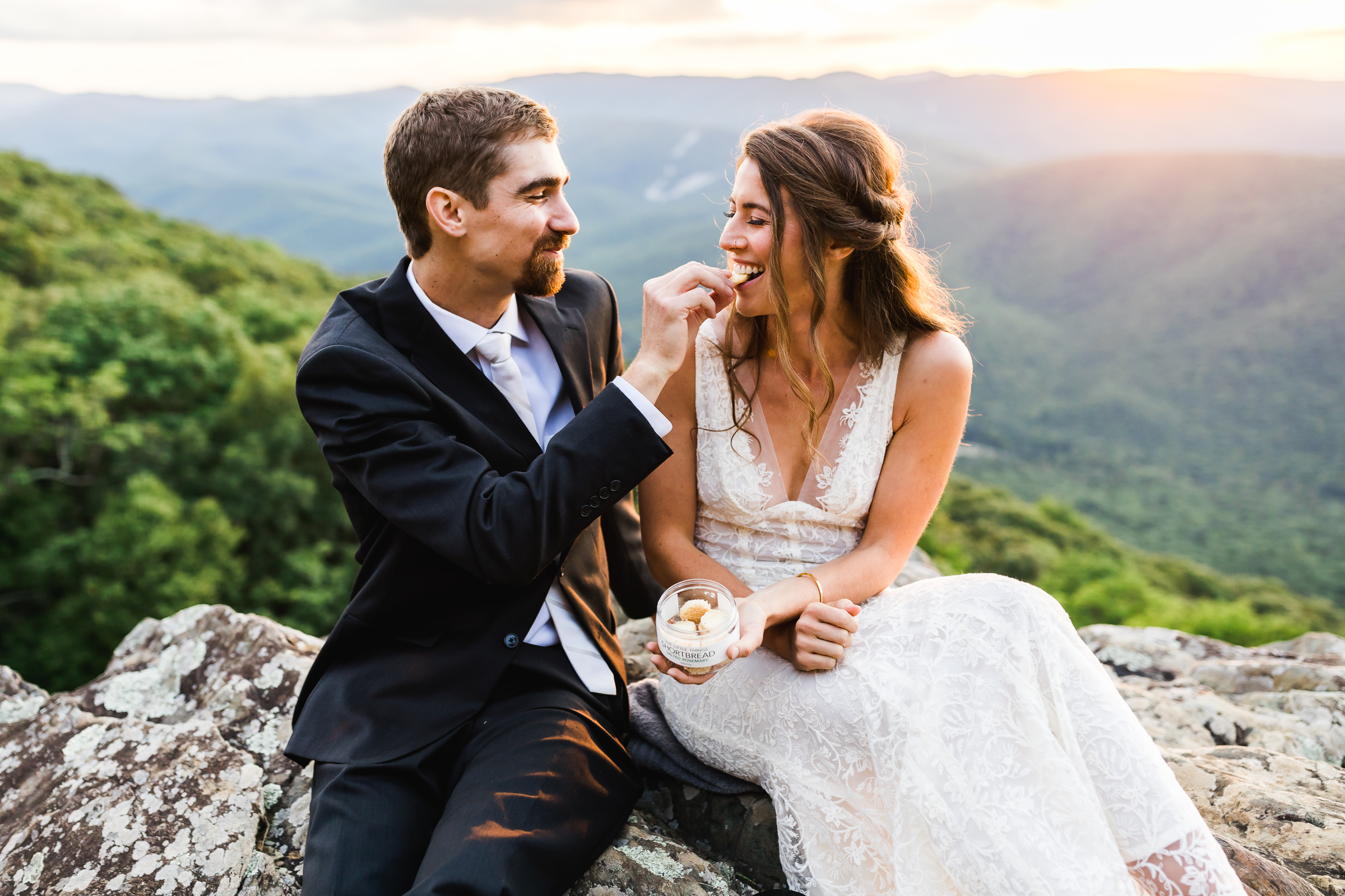 Groom feeding cookies to bride on mountaintop - photo by Xiaoqi Li Photography