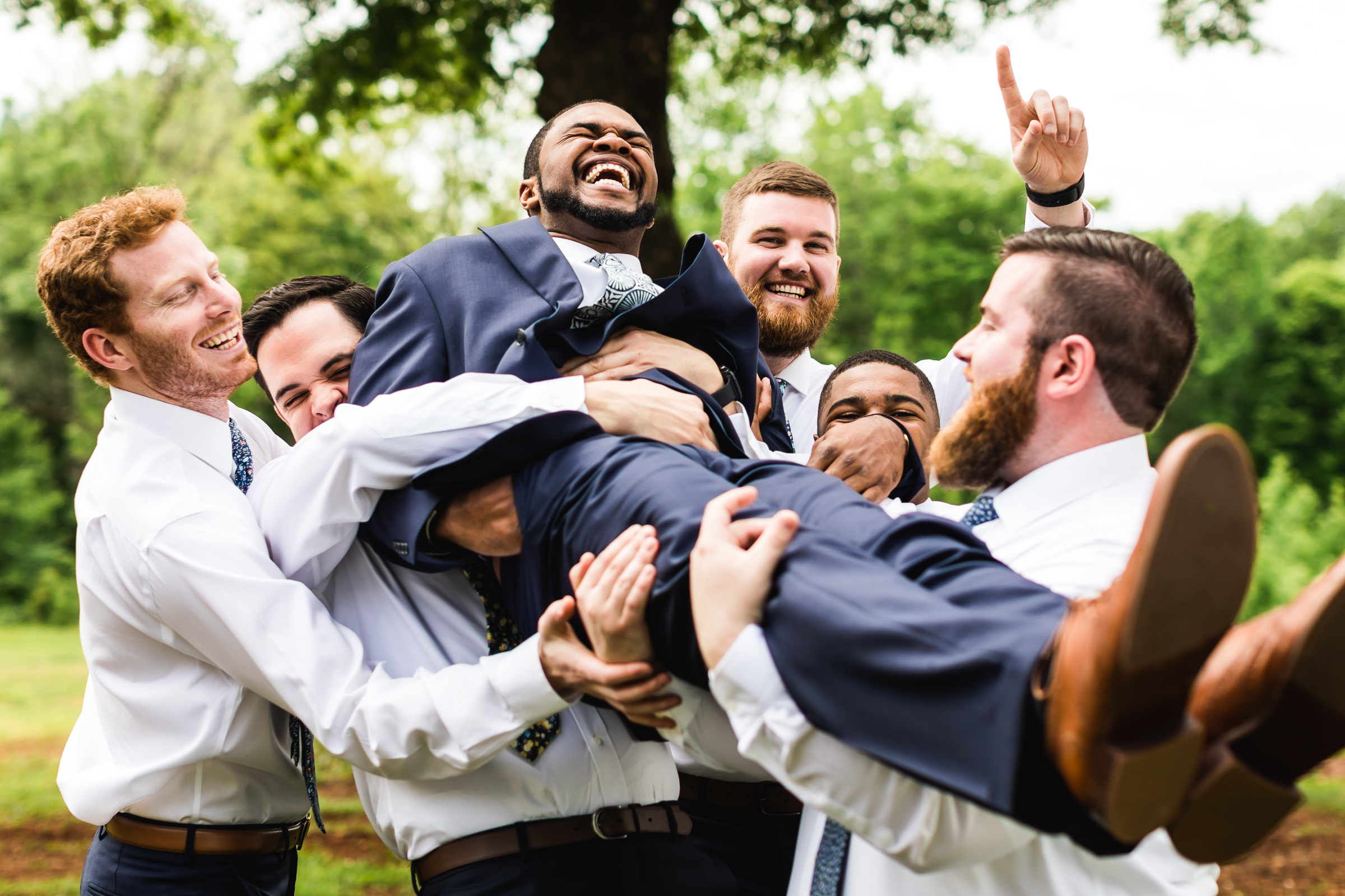 Groomsmen carrying supine groom - photo by Xiaoqi Li Photography