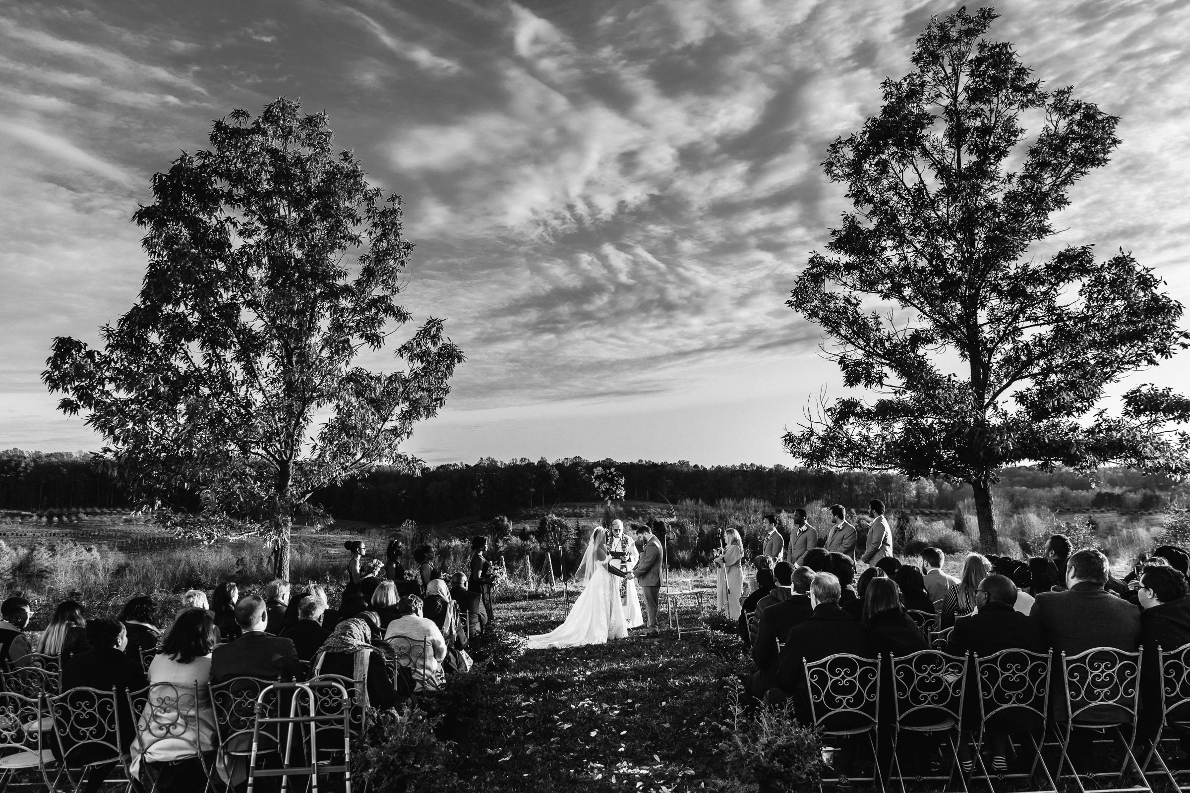 Outdoor ceremony under cloudy skies - photo by Xiaoqi Li Photography