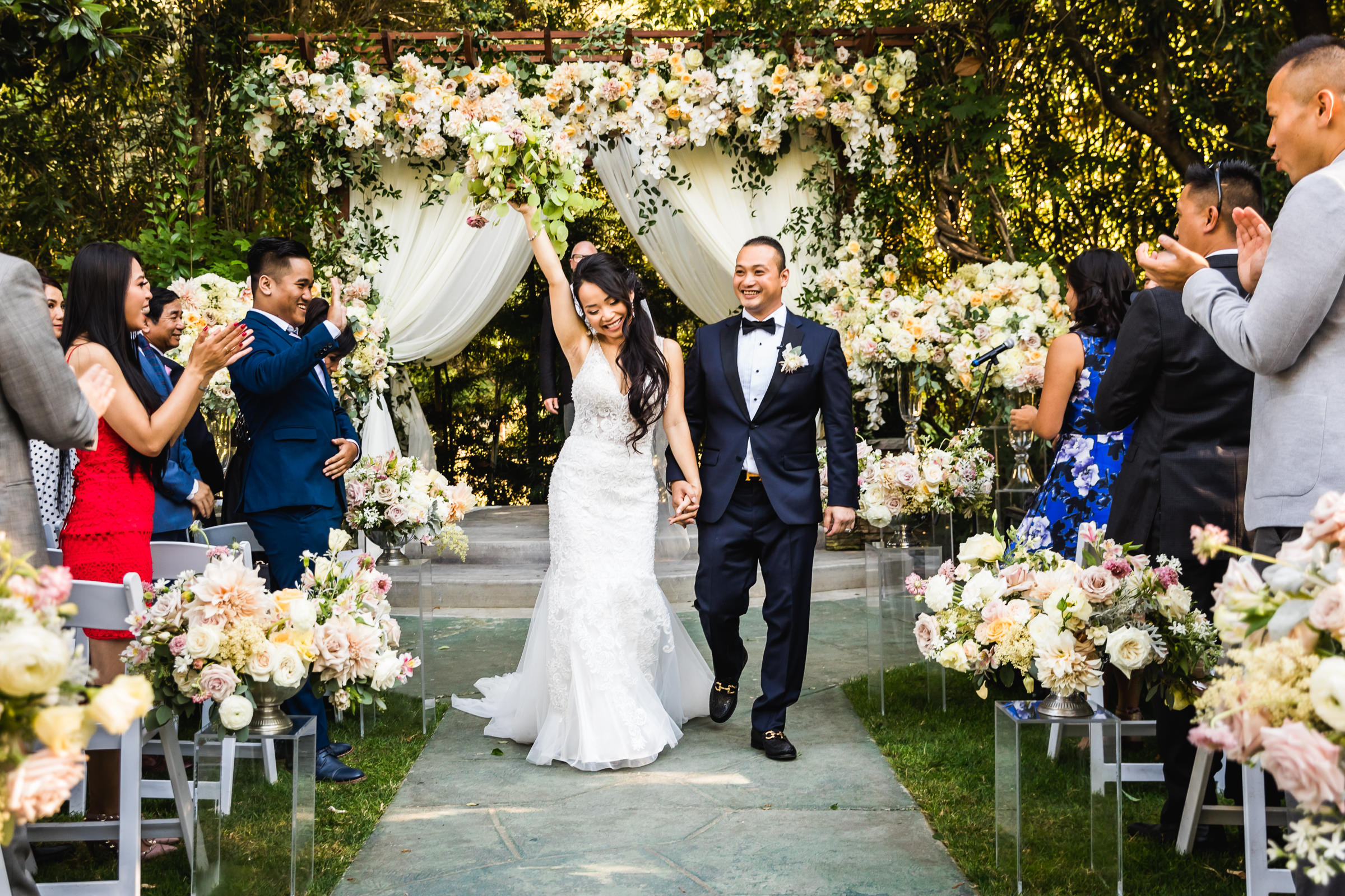 Outdoor couple recessional against profusion of flowers - photo by Xiaoqi Li Photography