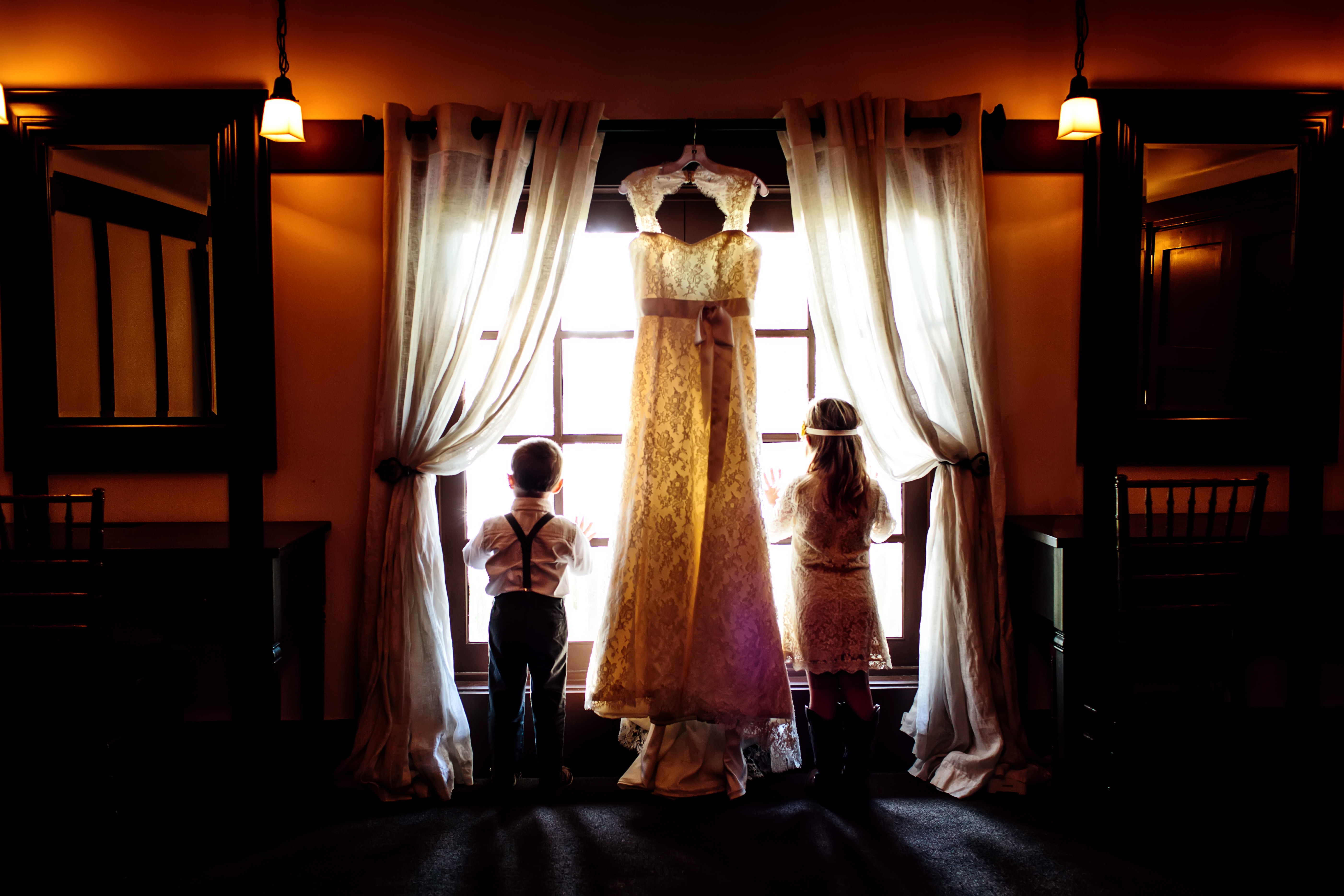 Children and hanging bridal gown at window - photo by Rayan Anastor Photography