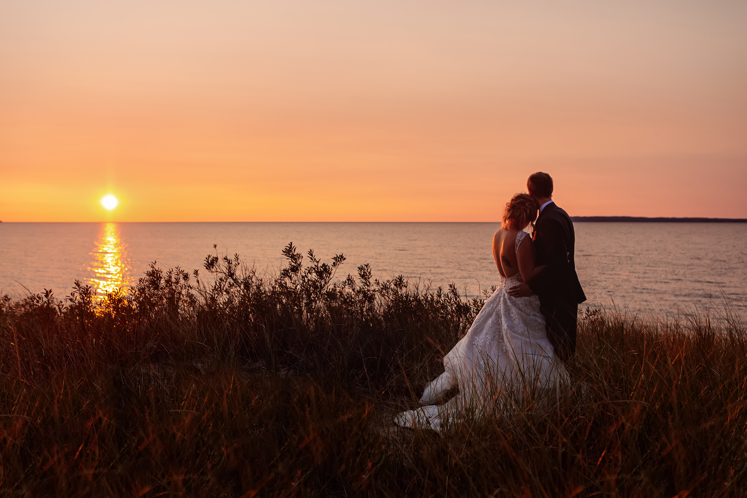 Couple gazes at setting sun over lake - photo by Rayan Anastor Photography