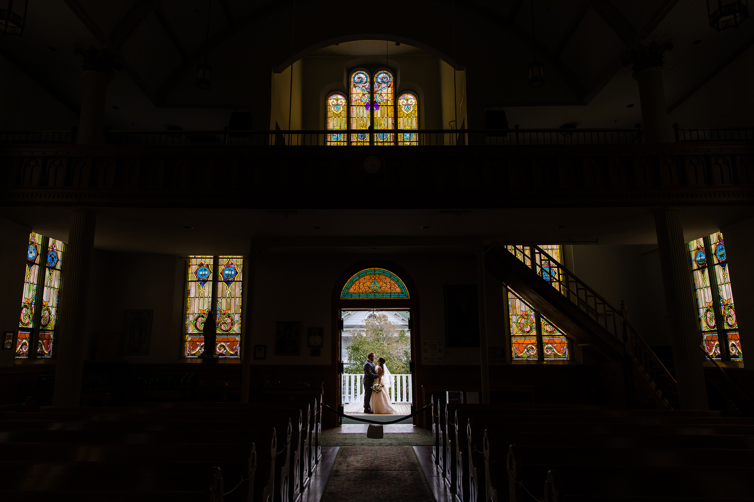 Couple in church doorway with stained glass - photo by Rayan Anastor Photography