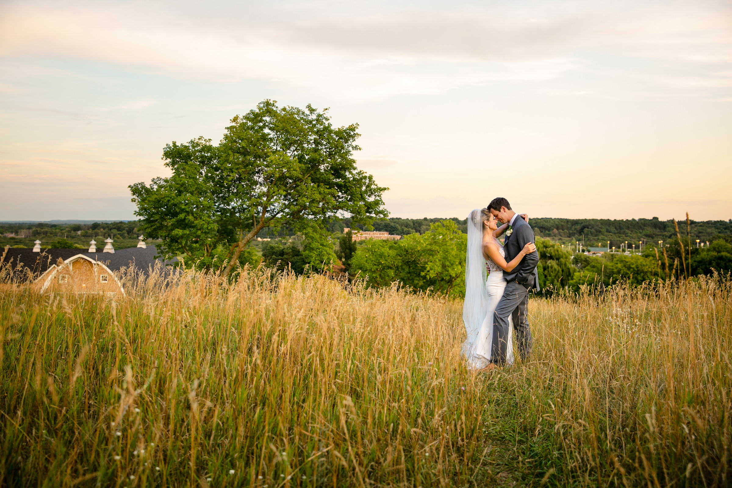 Couple pose in grassy field at historic barns park - photo by Rayan Anastor Photography