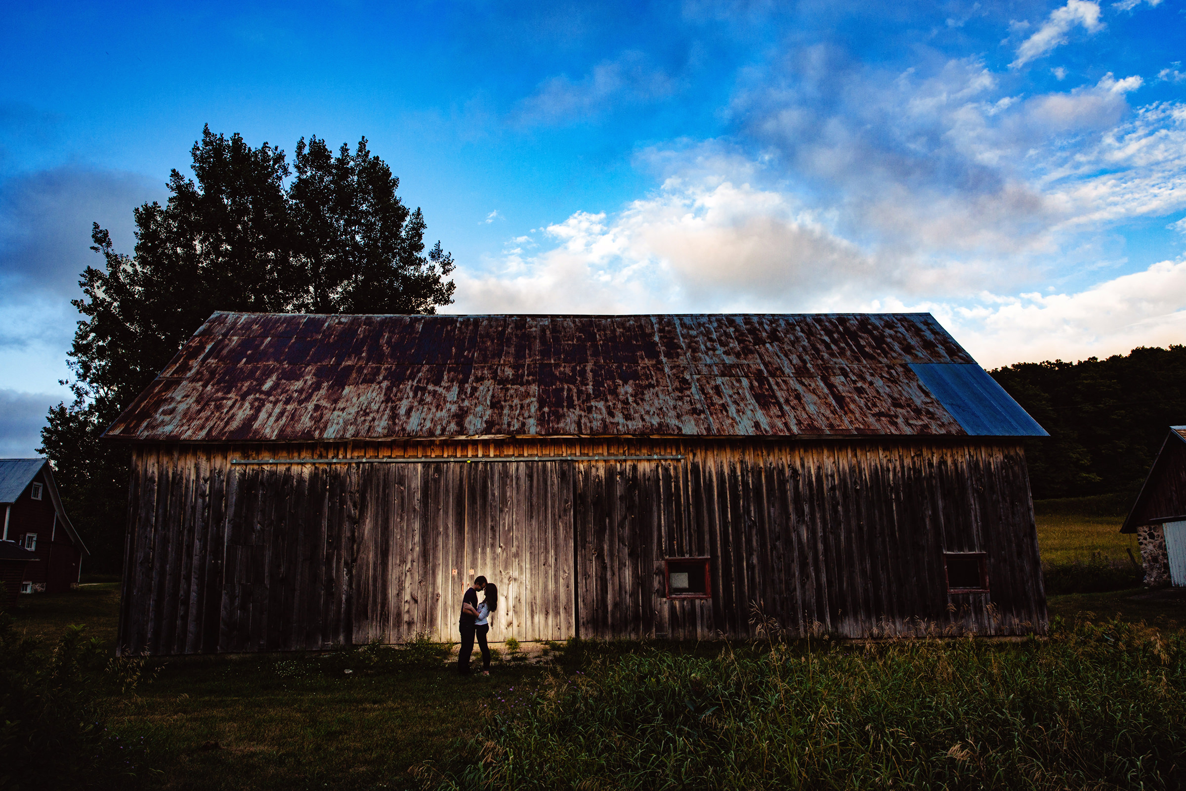 Spotlight on couple against rustic farm building - photo by Rayan Anastor Photography