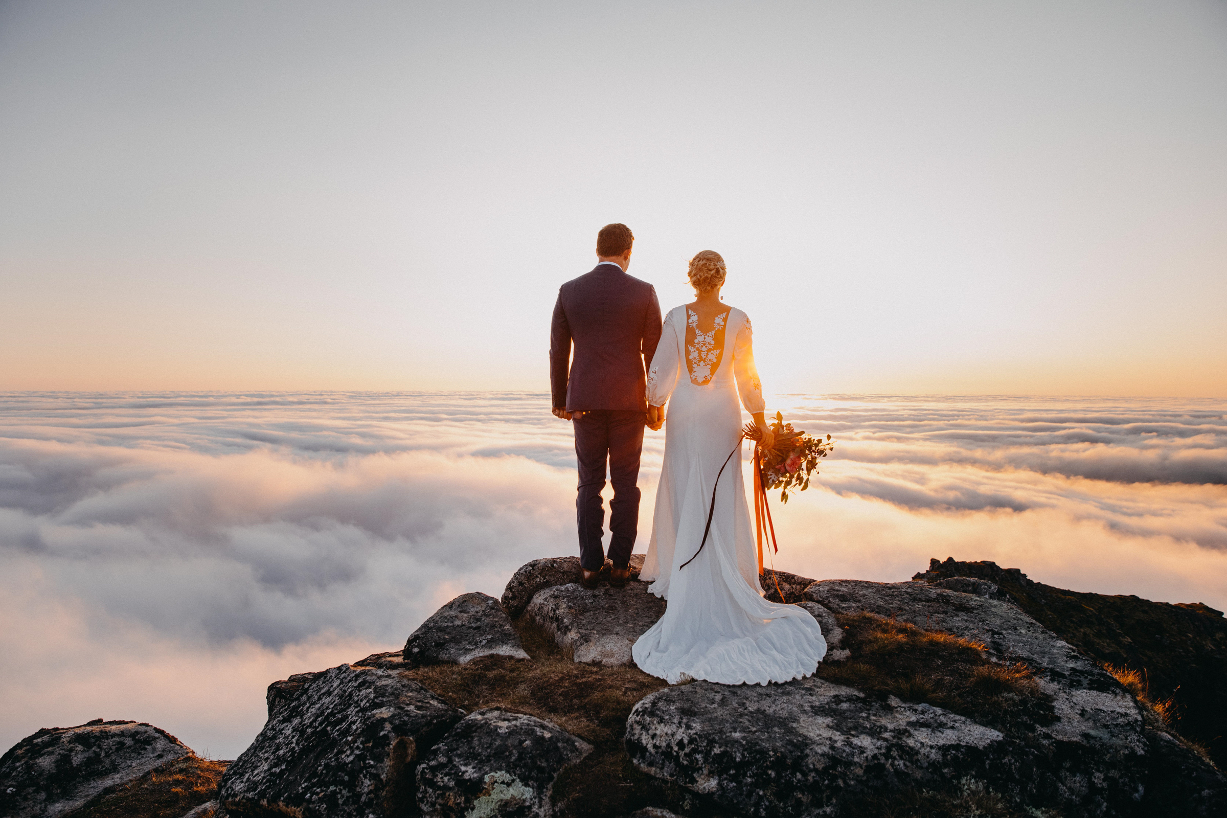 Back view of couple at sunset above the clouds in Lofoten Norway - photo by Christin Eide Photography