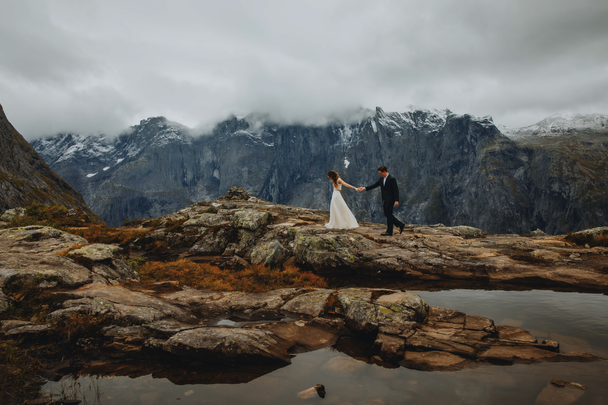 Bride leads groom through rocky landscape against mountains at Rauma Norway - photo by Christin Eide Photography