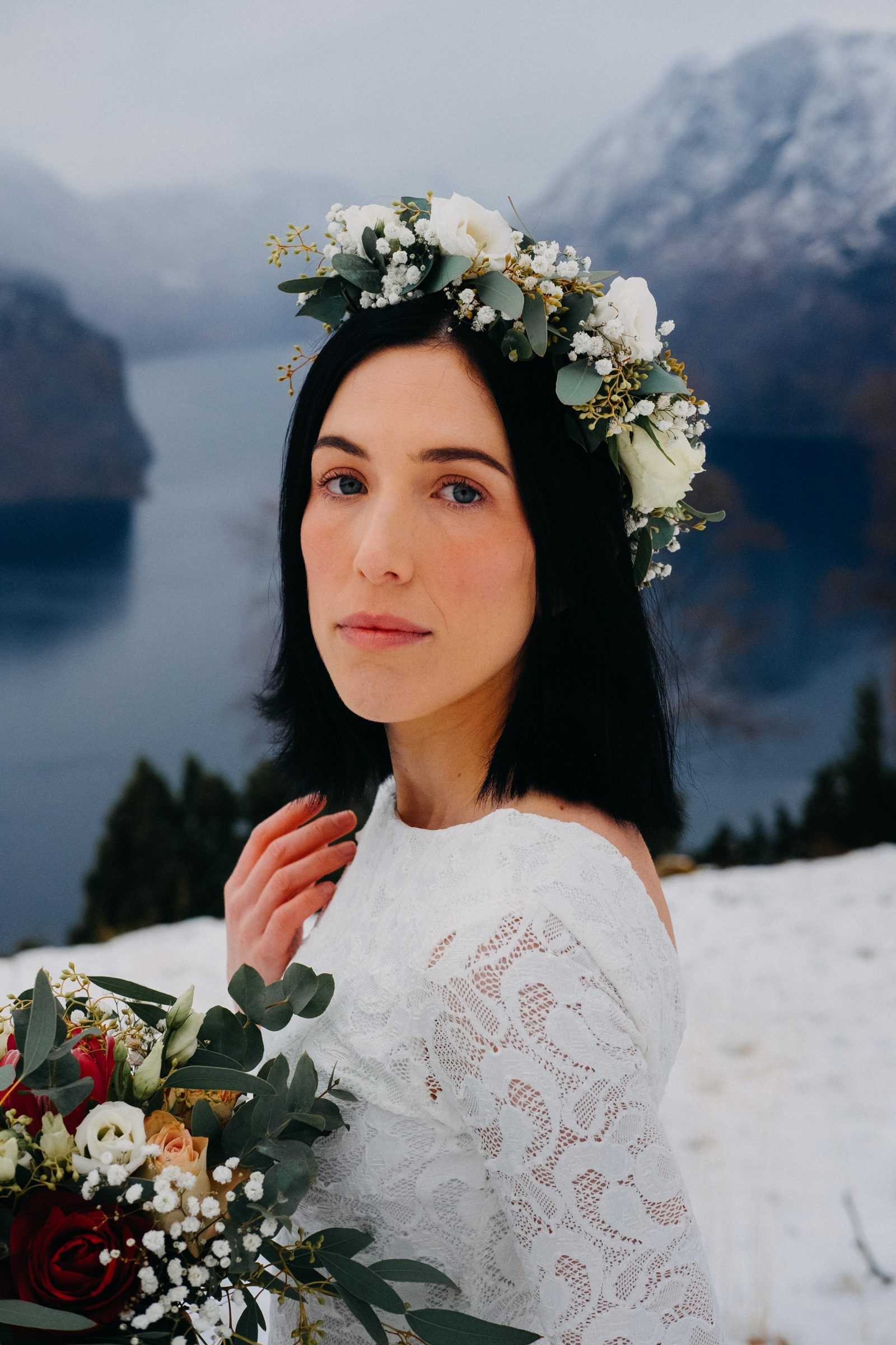 Bride portrait with floral crown and bouquet against snowy mountains and fjord - photo by Christin Eide Photography