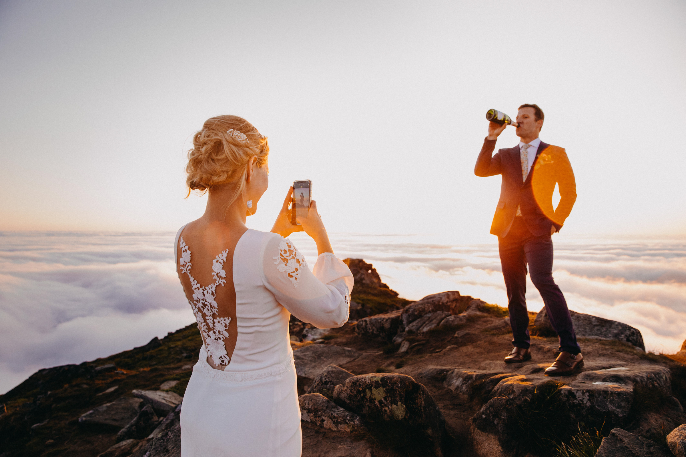 Bride shoots groom drinking from bottle at mountaintop Lofoten Norway - photo by Christin Eide Photography