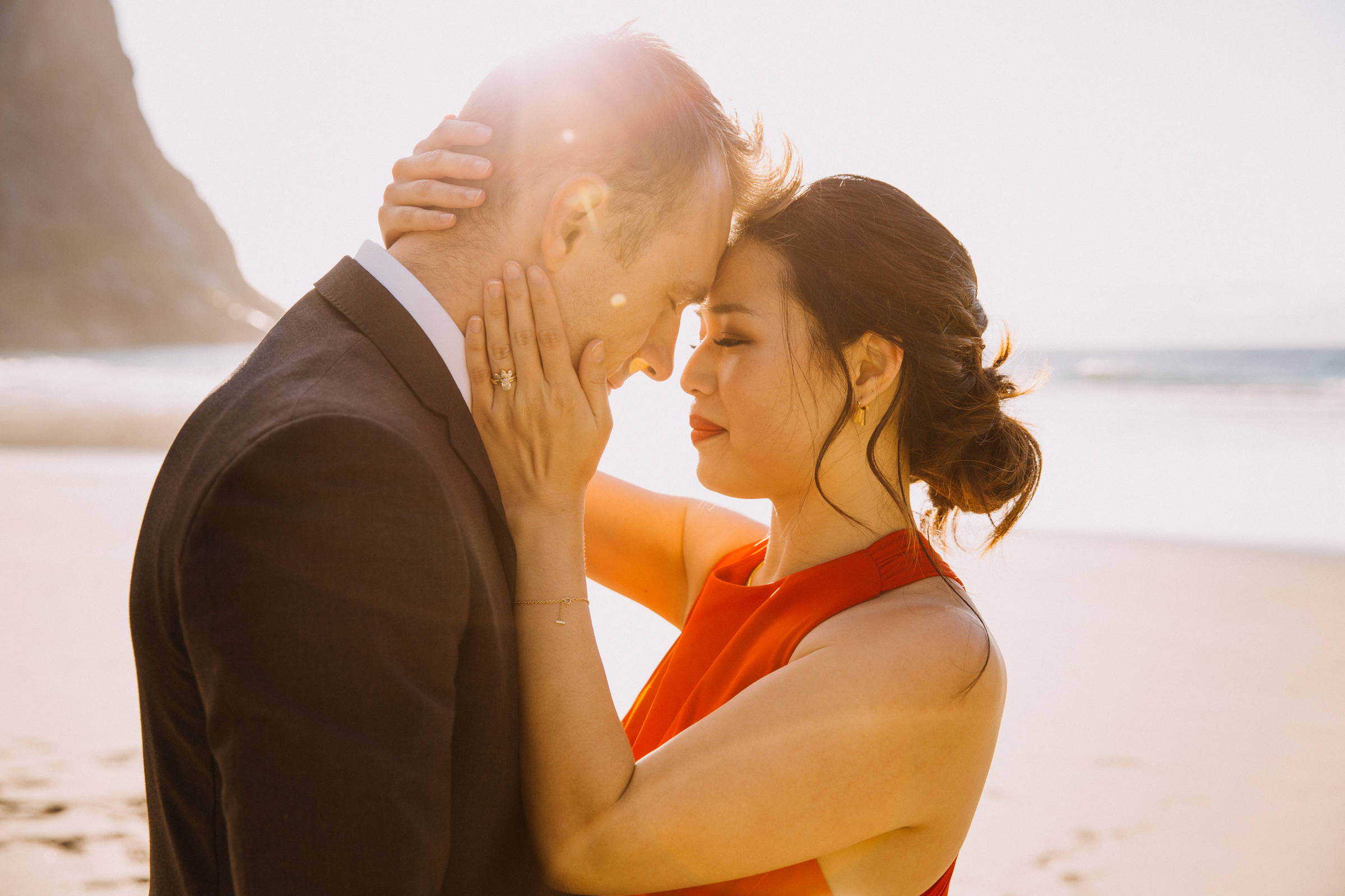 Elopement couple on Lofoten Norway beach bride in red dress  - photo by Christin Eide Photography