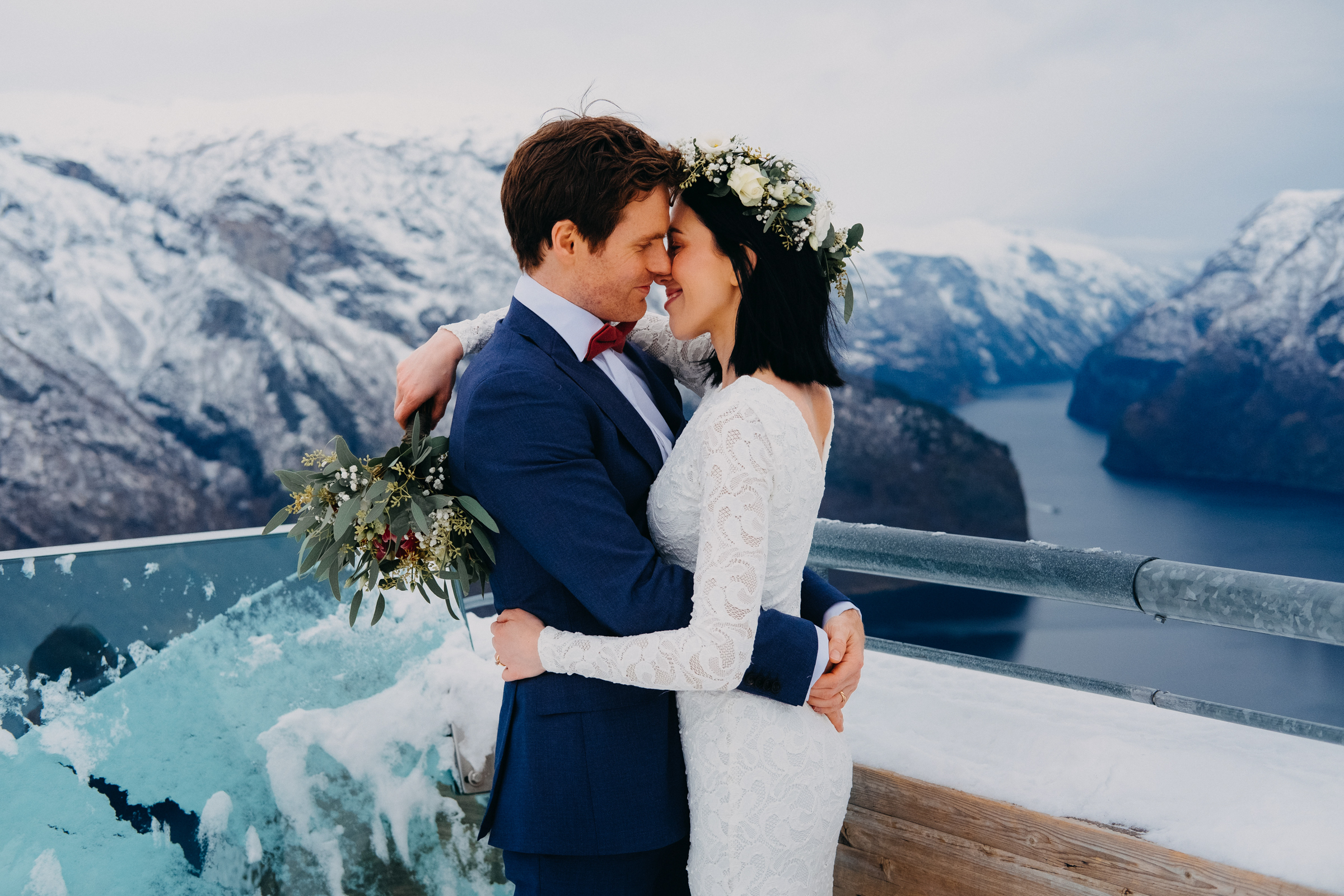 Couple embrace on bridge against snowy mountains and fjord Aurland Norway - photo by Christin Eide Photography