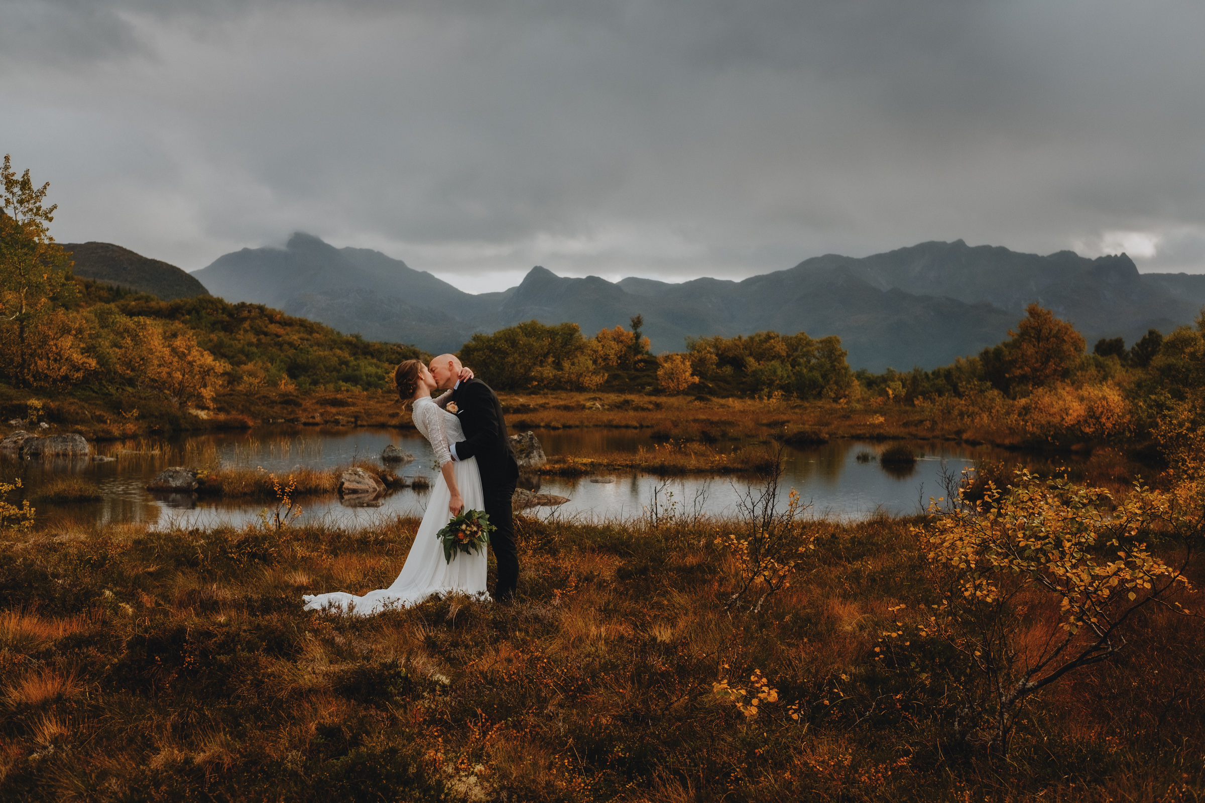 Couple kiss at edge of loch with autumn colors in Norway - photo by Christin Eide Photography