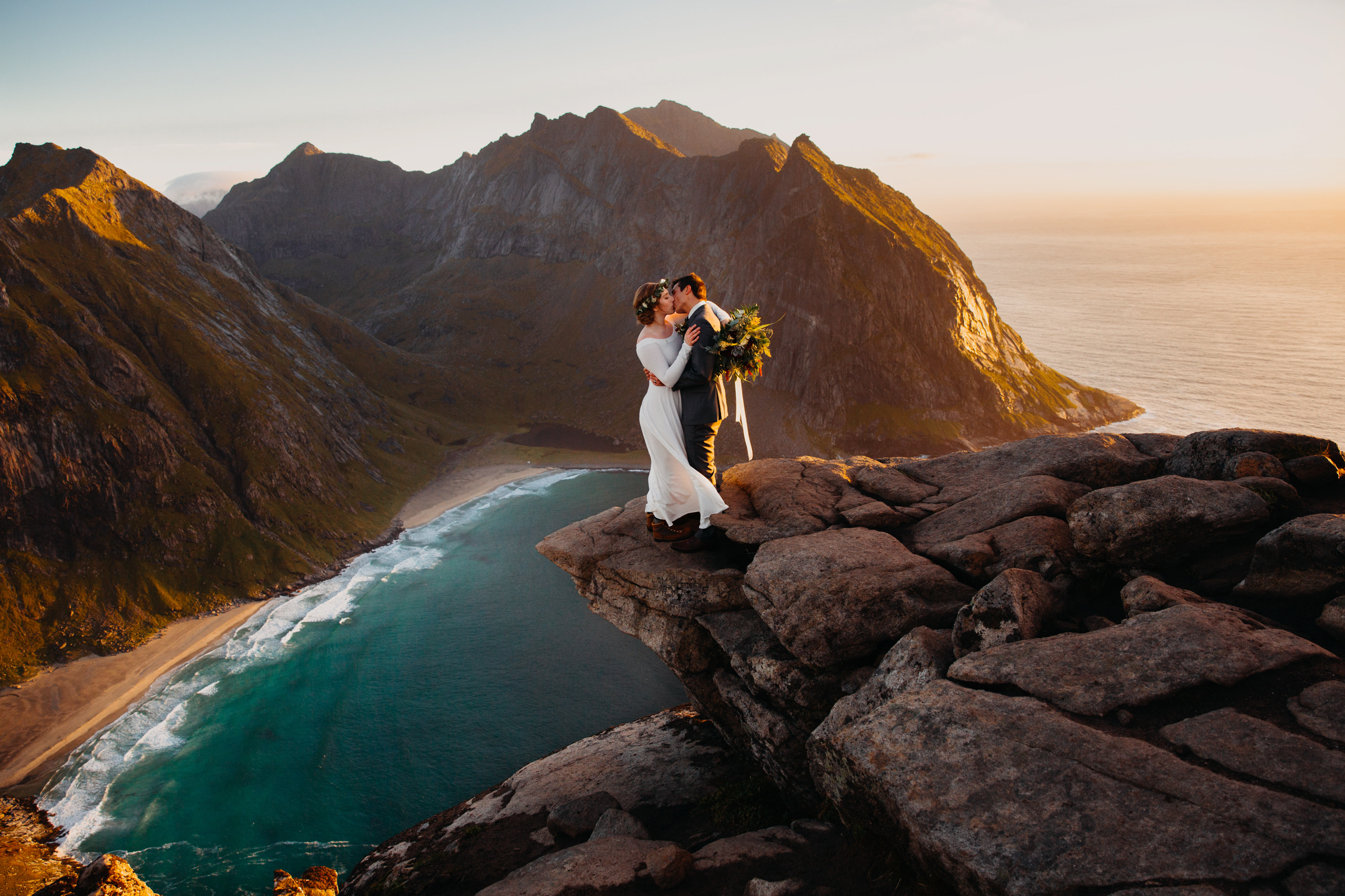 Couple on precipice against mountains and sea at Lofoten Norway - photo by Christin Eide Photography