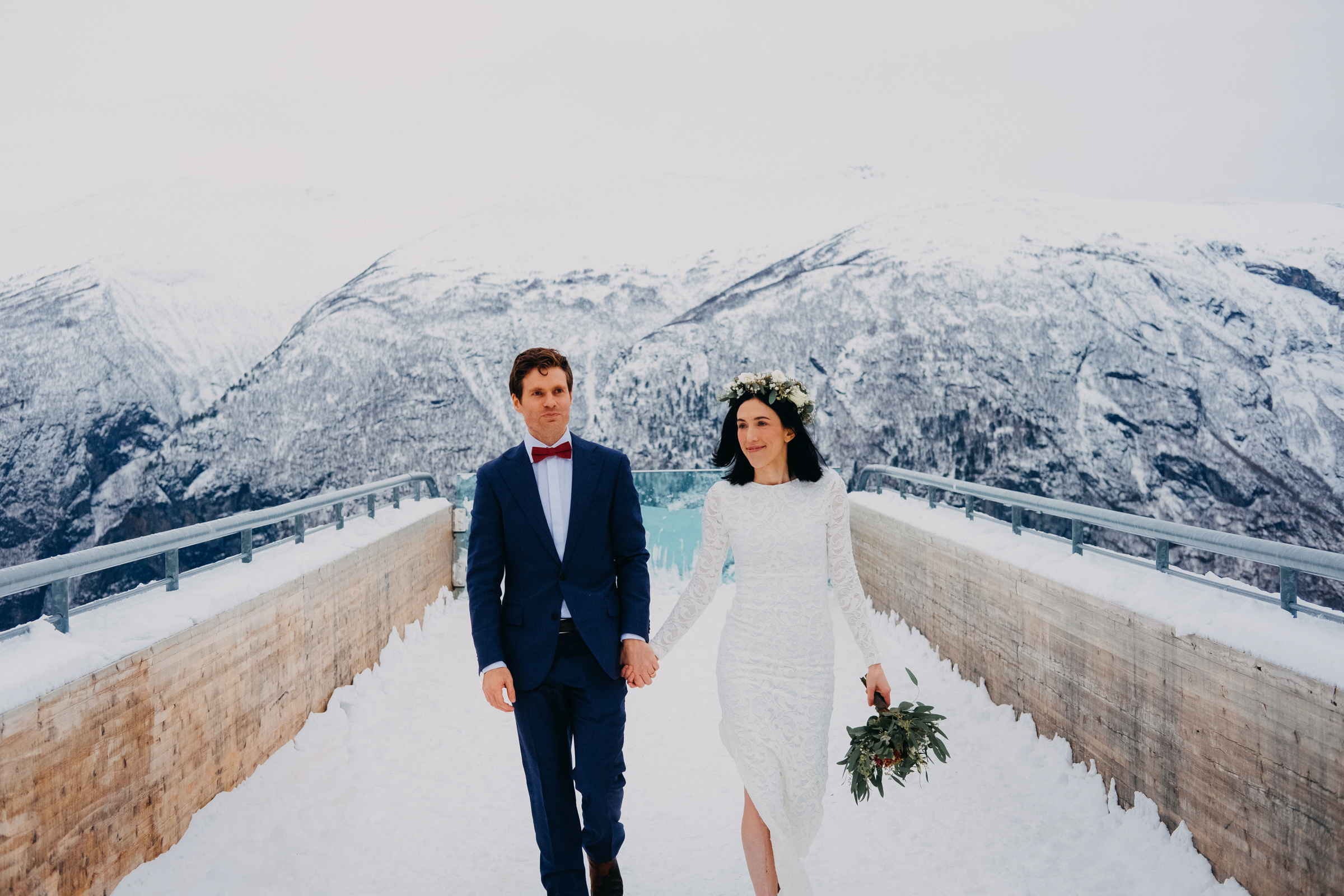 Couple walking on bridge against snowy mountains Aurland Norway - photo by Christin Eide Photography