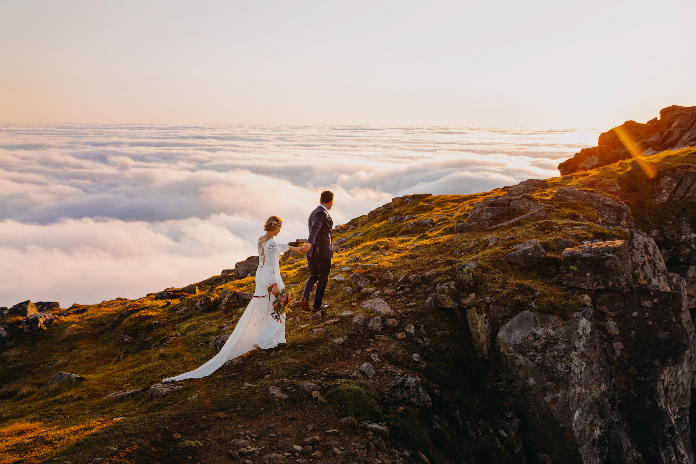Couple walking on cliff above the clouds - photo by Christin Eide Photography