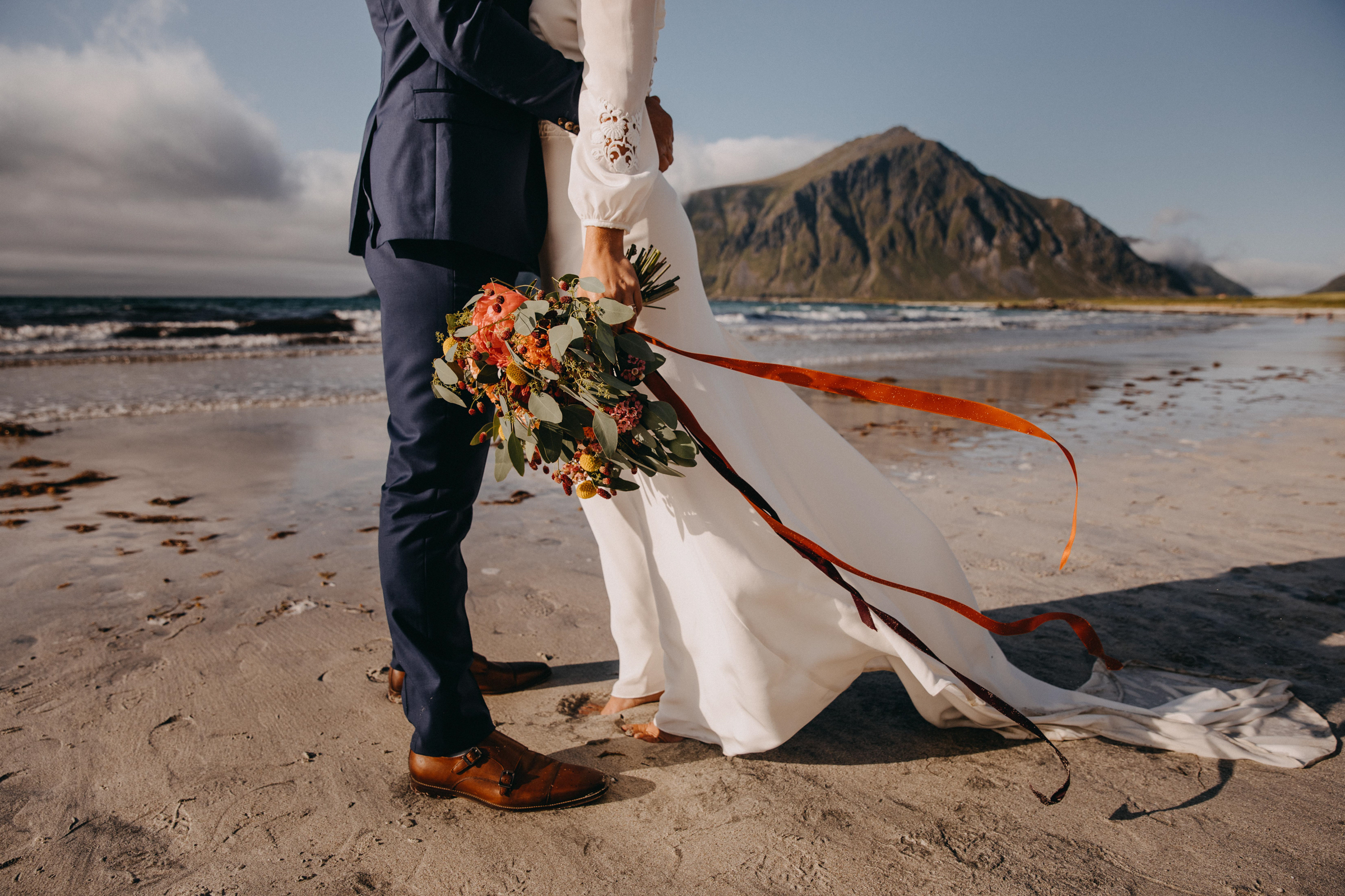 Cropped portrait of couple on epic Norway beach against mountain and clouds- photo by Christin Eide Photography