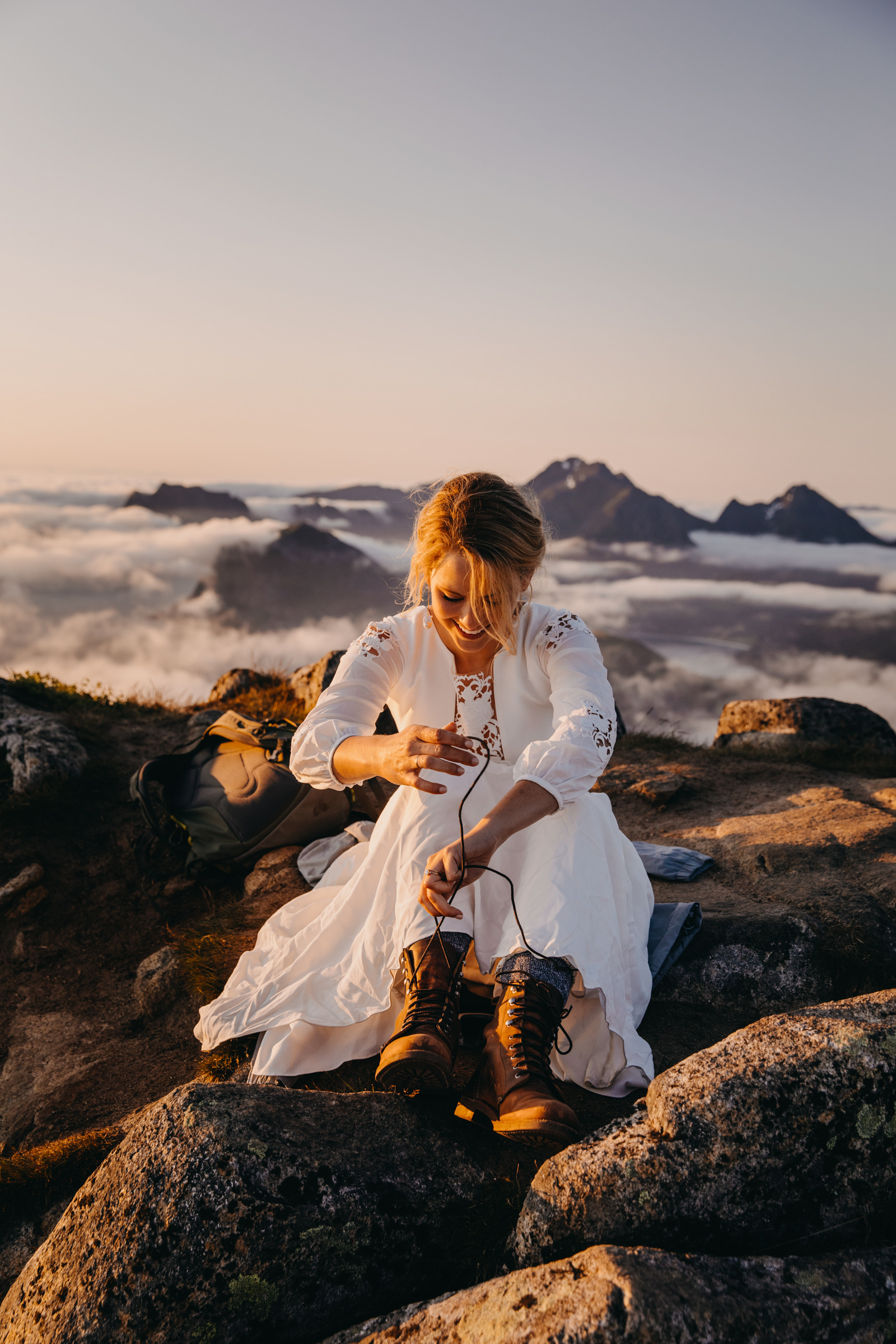 Elopement bride tying her boots on rocky outcrop above the clouds - photo by Christin Eide Photography