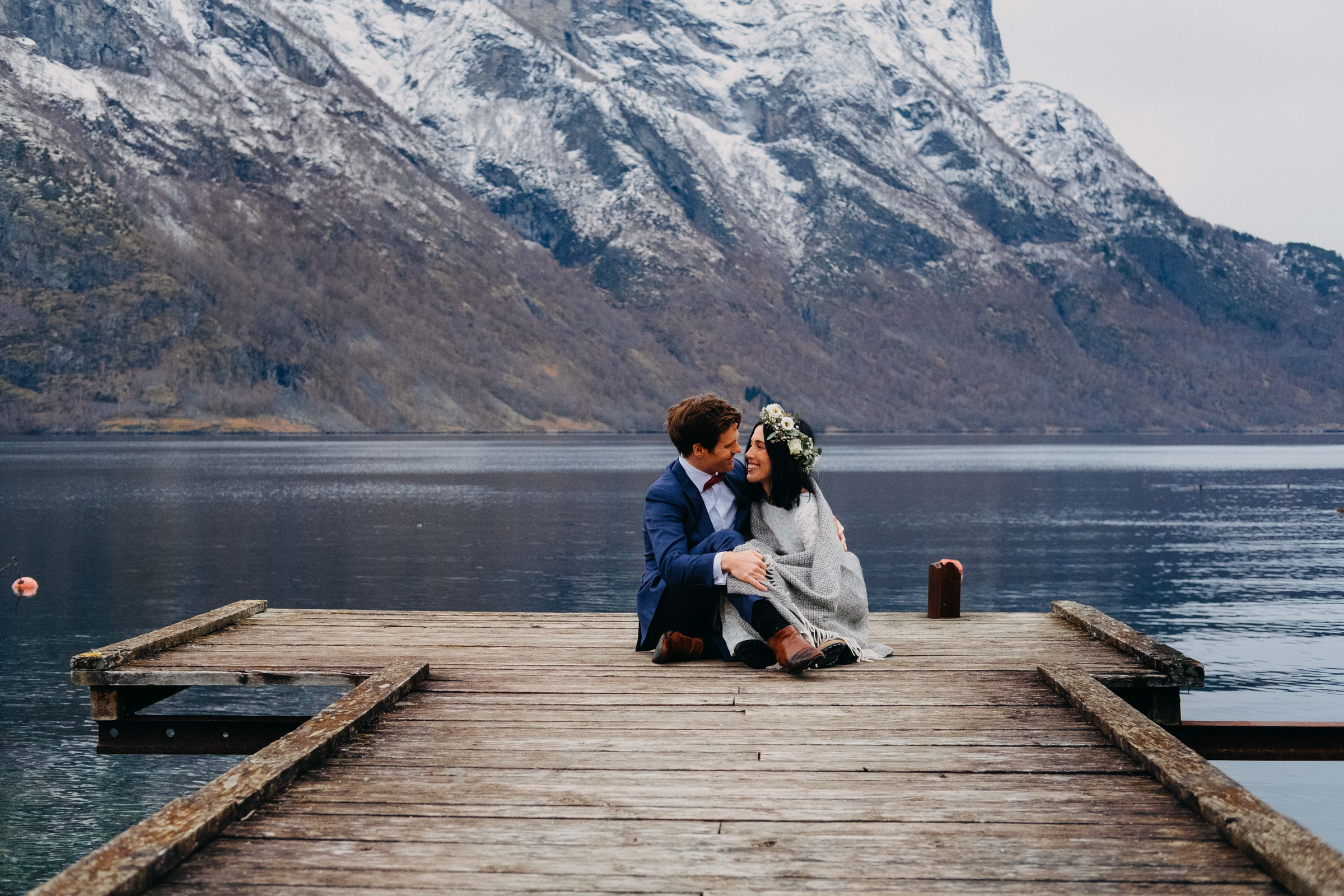 Elopement couple sitting on dock against mountains and fjord - photo by Christin Eide Photography