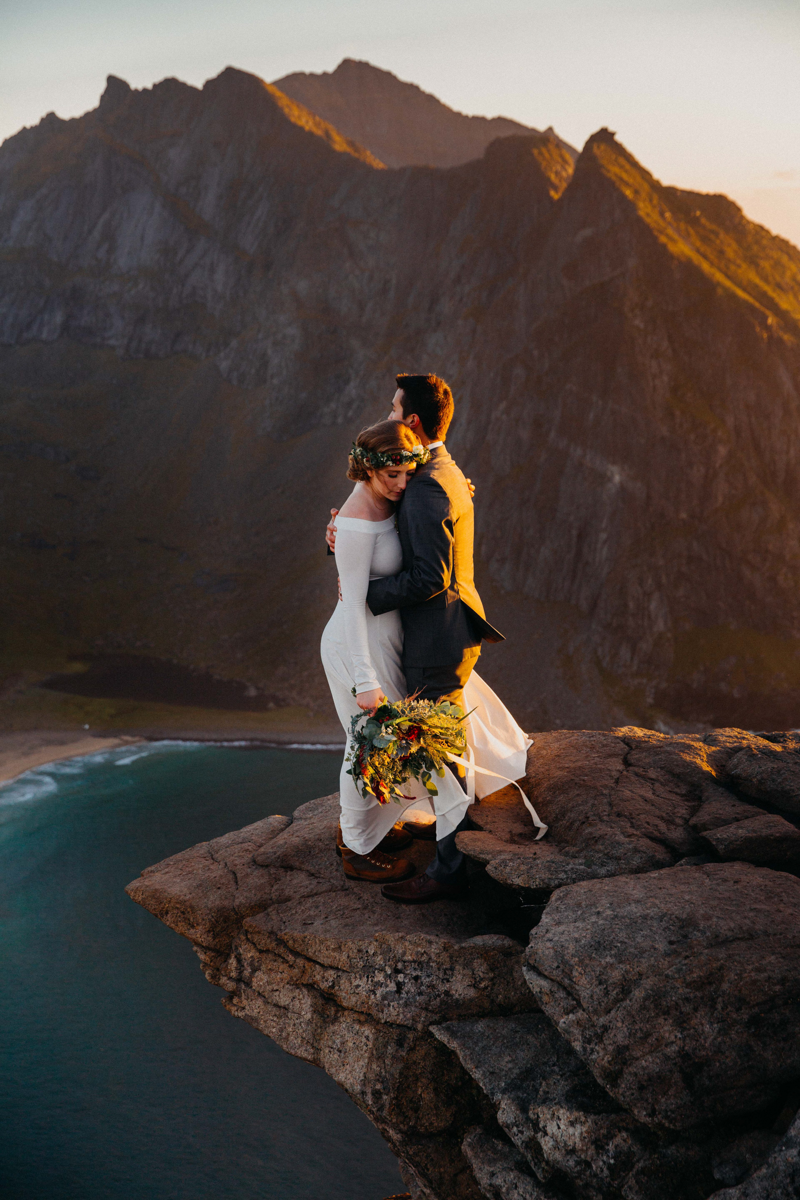 Engagement couple embrace on precipice against mountains and sea - photo by Christin Eide Photography