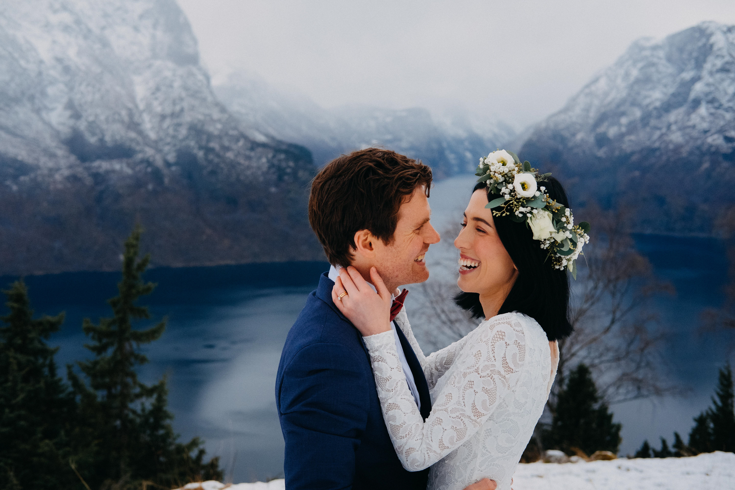 Face to face smiling couple portrait against snowy mountains and fjord - photo by Christin Eide Photography